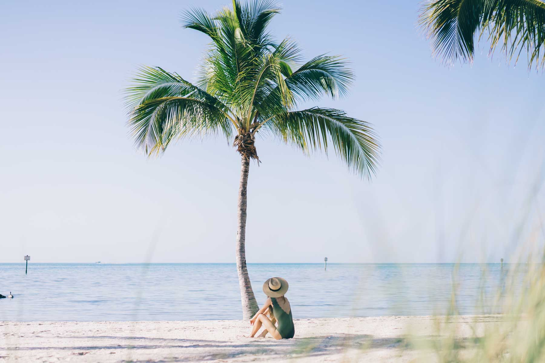 Jess Ann Kirby relaxes under the palm trees on Smathers Beach in Key West, Florida