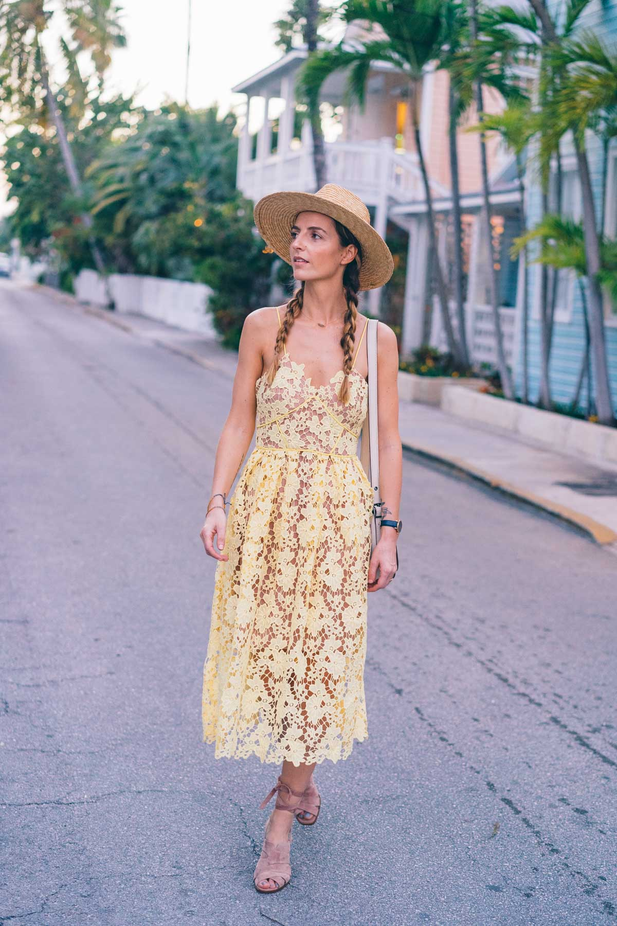 Jess Kirby wears a yellow lace midi dress and blush lace up heels in Key West