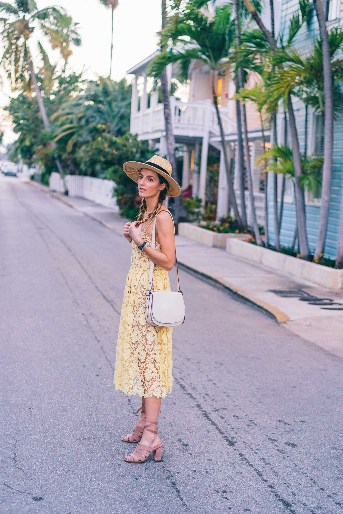 Jess Kirby in Key West wearing a yellow lace midi dress from Anthropologie and blush suede heels