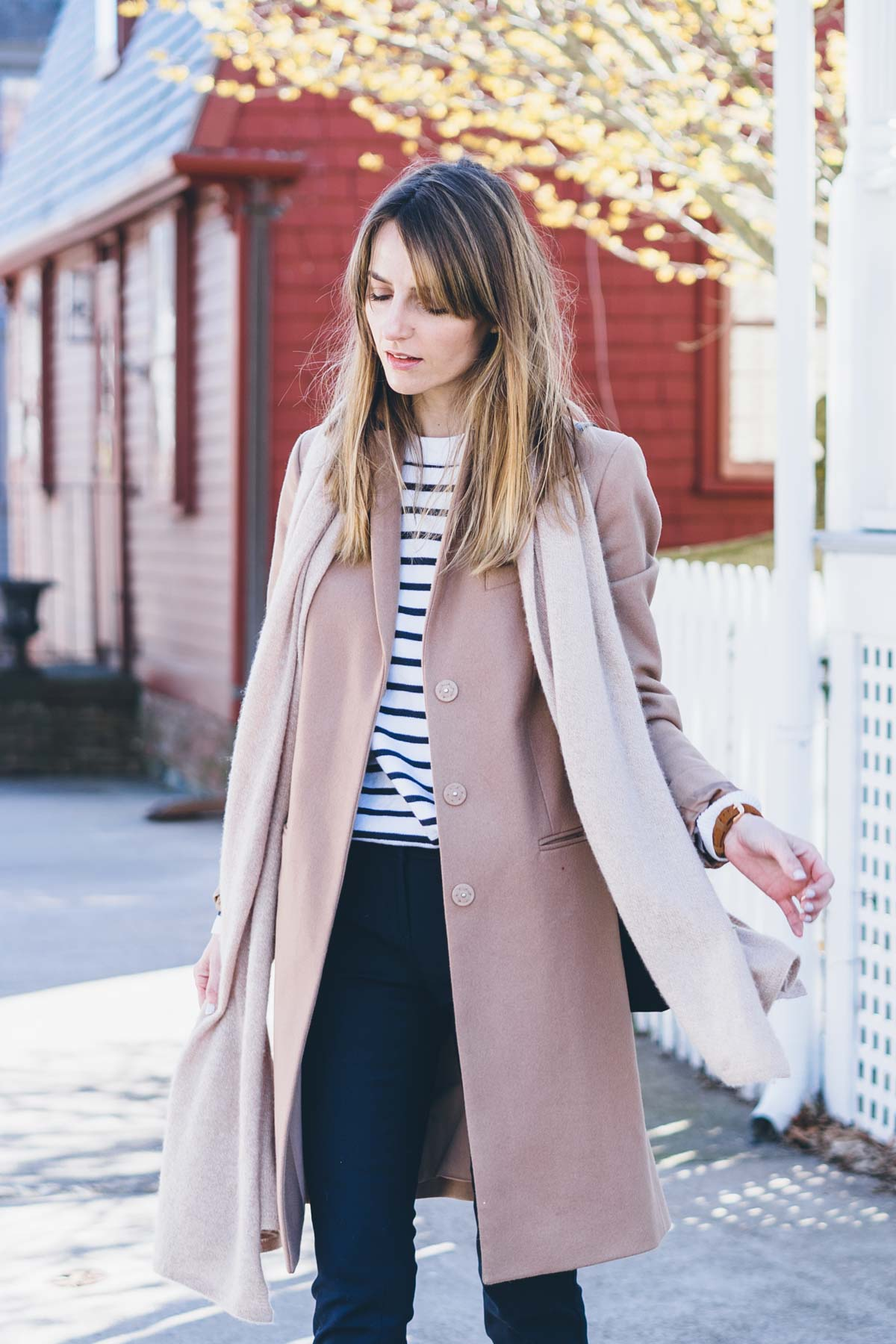 Jess Ann Kirby in a camel coat and striped sweater for spring