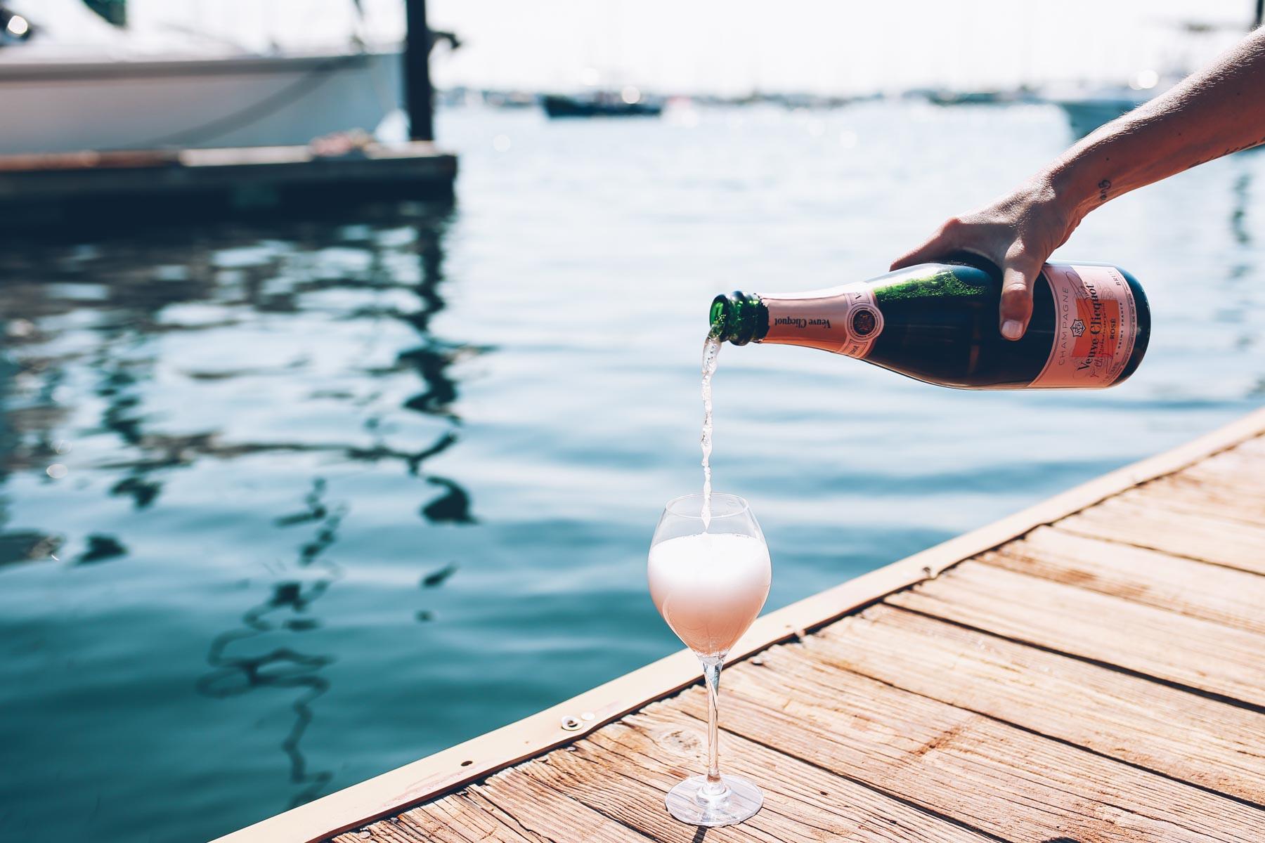 Jess Ann Kirby pours a glass of veuve cliquot in Newport Rhode Island