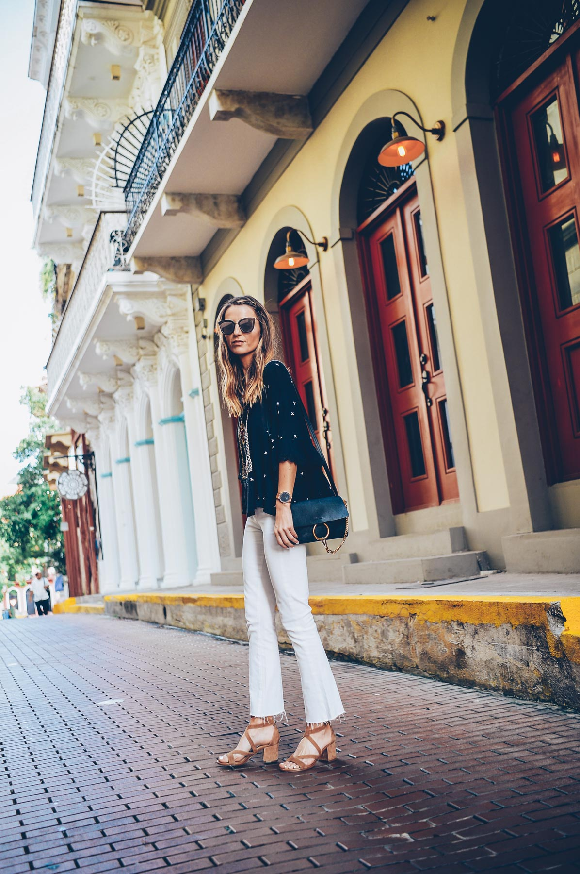 Jess Kirby styling white jeans and lace up sandals with a boho blouse for summer