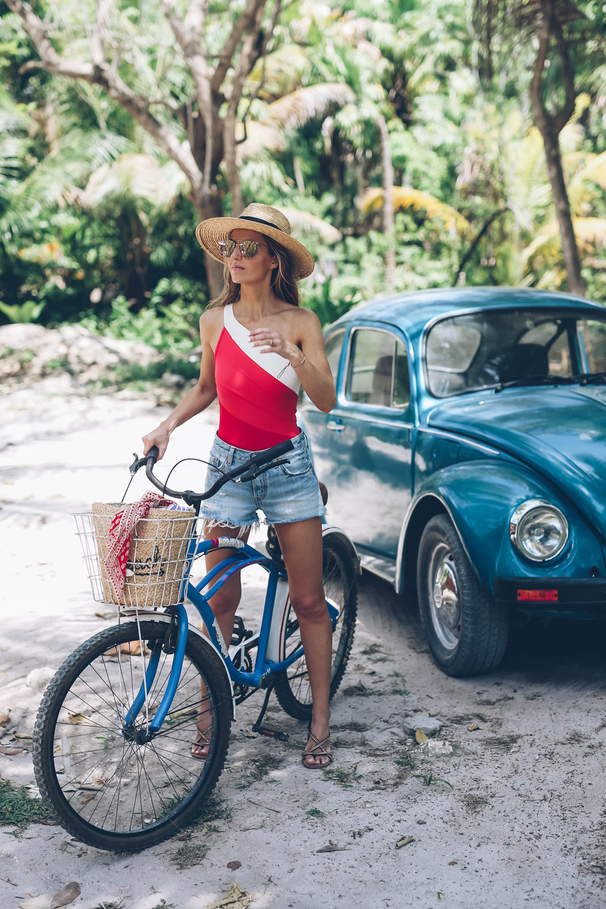 Jess Ann Kirby wears a one shoulder swimsuit, Levi's cut off shorts and a straw panama hat in Tulum, Mexico