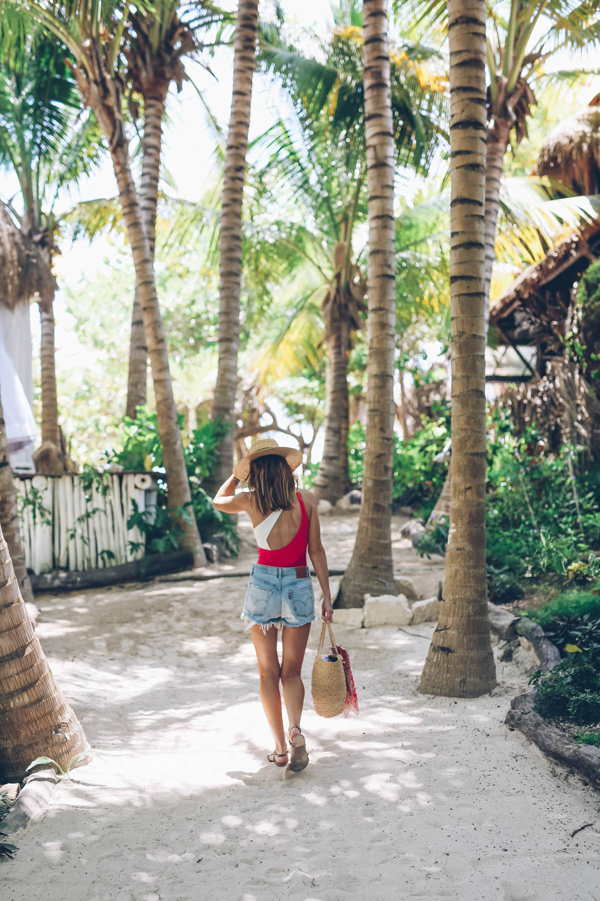 Jess Ann Kirby explores Tulum Mexico in cut-off shorts and a bright one piece bathing suit