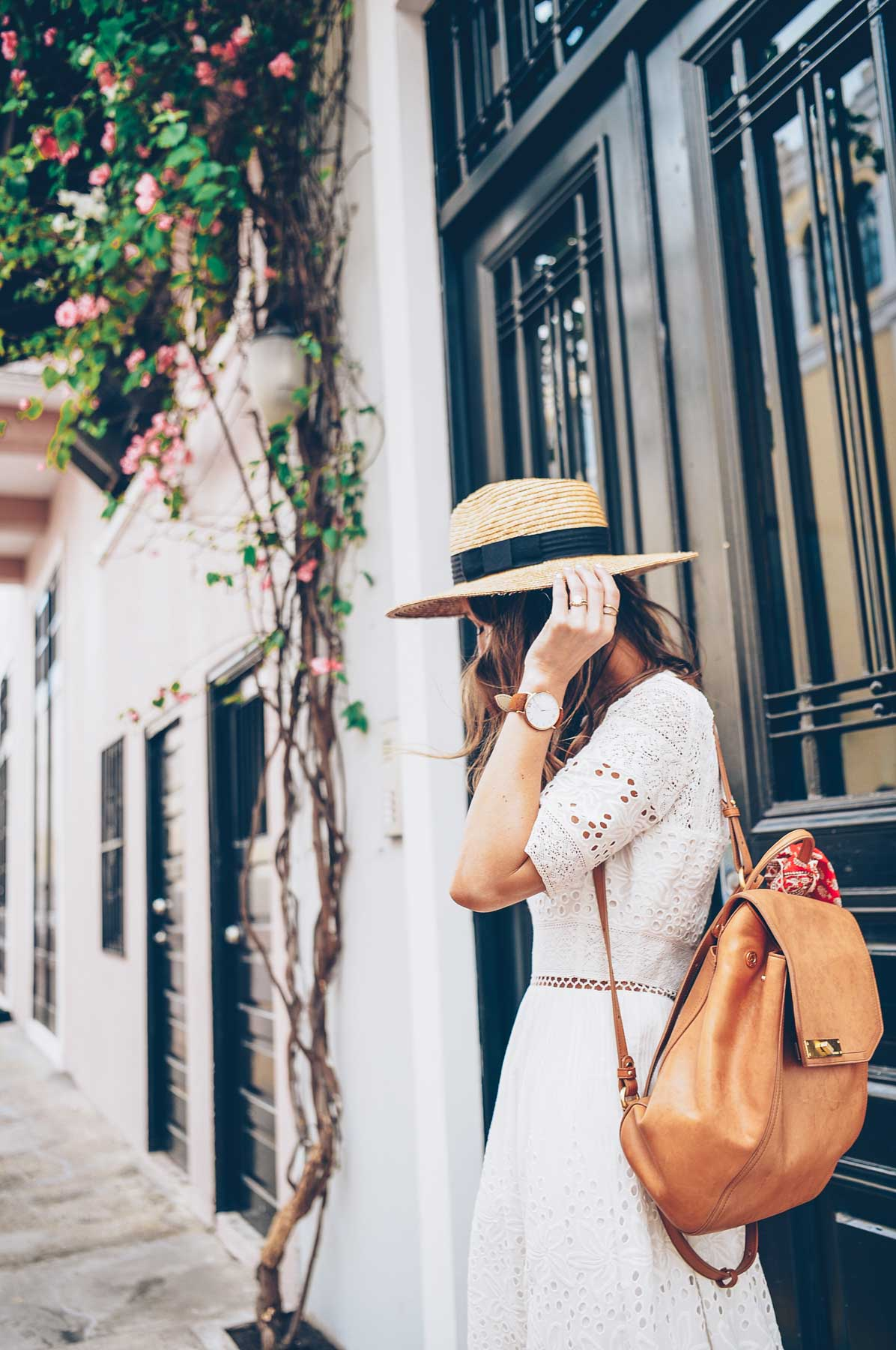 Jess Kirby wearing the Brahmin Southcoast backpack and Panama Hat with a white dress