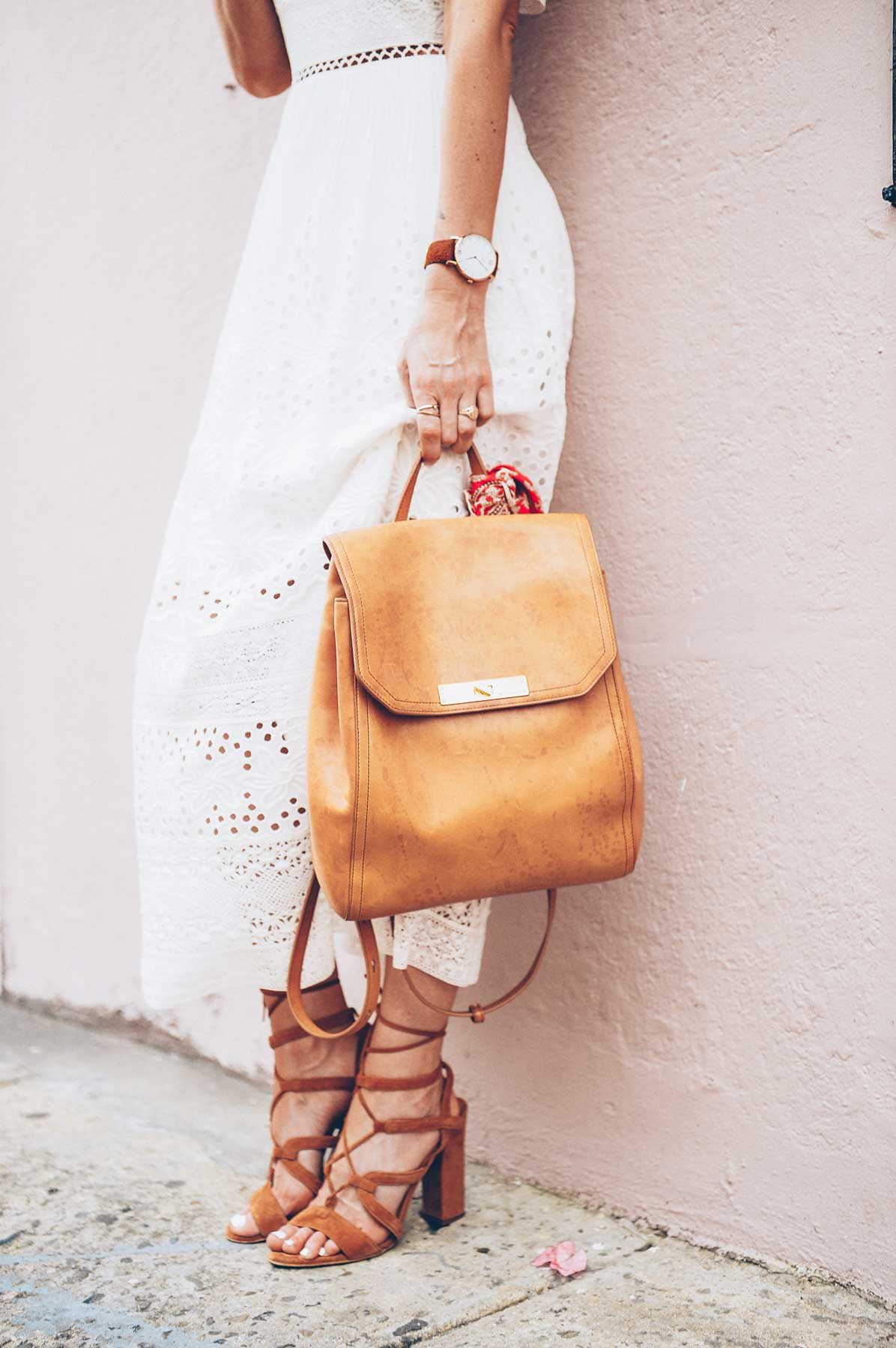 Jess Kirby wearing the Brahmin Southcoast backpack with lace up heels and a white dress