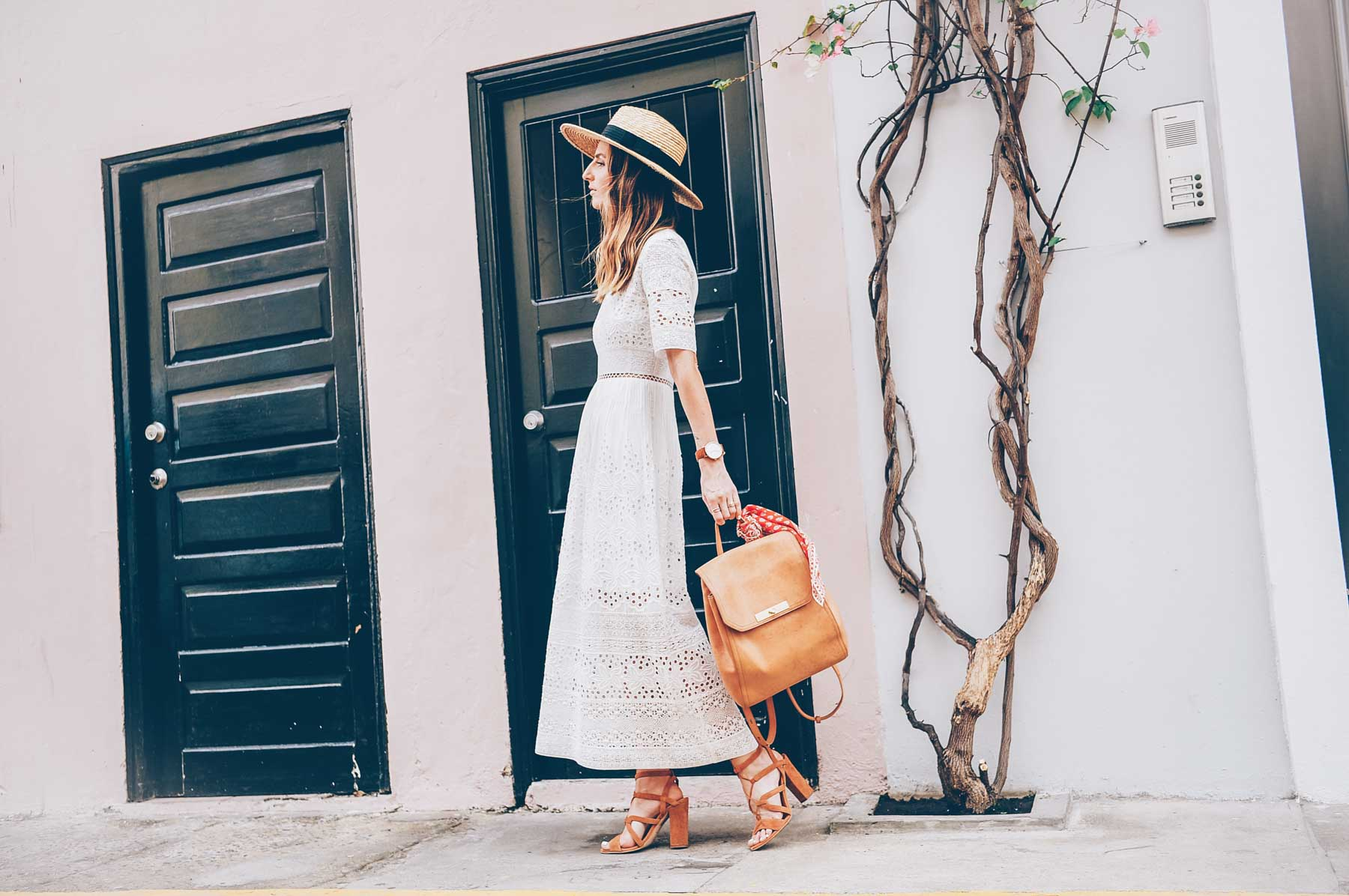 Jess Kirby styling a white embroidered maxi dress and tan leather backpack for summer