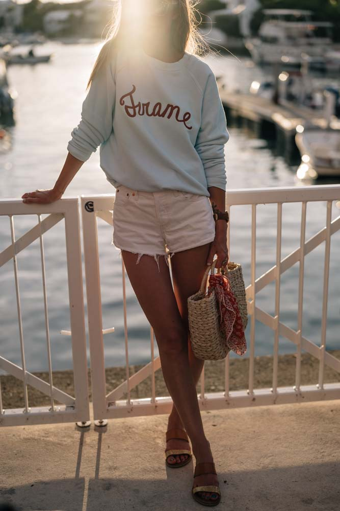 Jess Ann Kirby enjoys a night by the water in Levi's jean shorts and the Frame Old School Sweatshirt