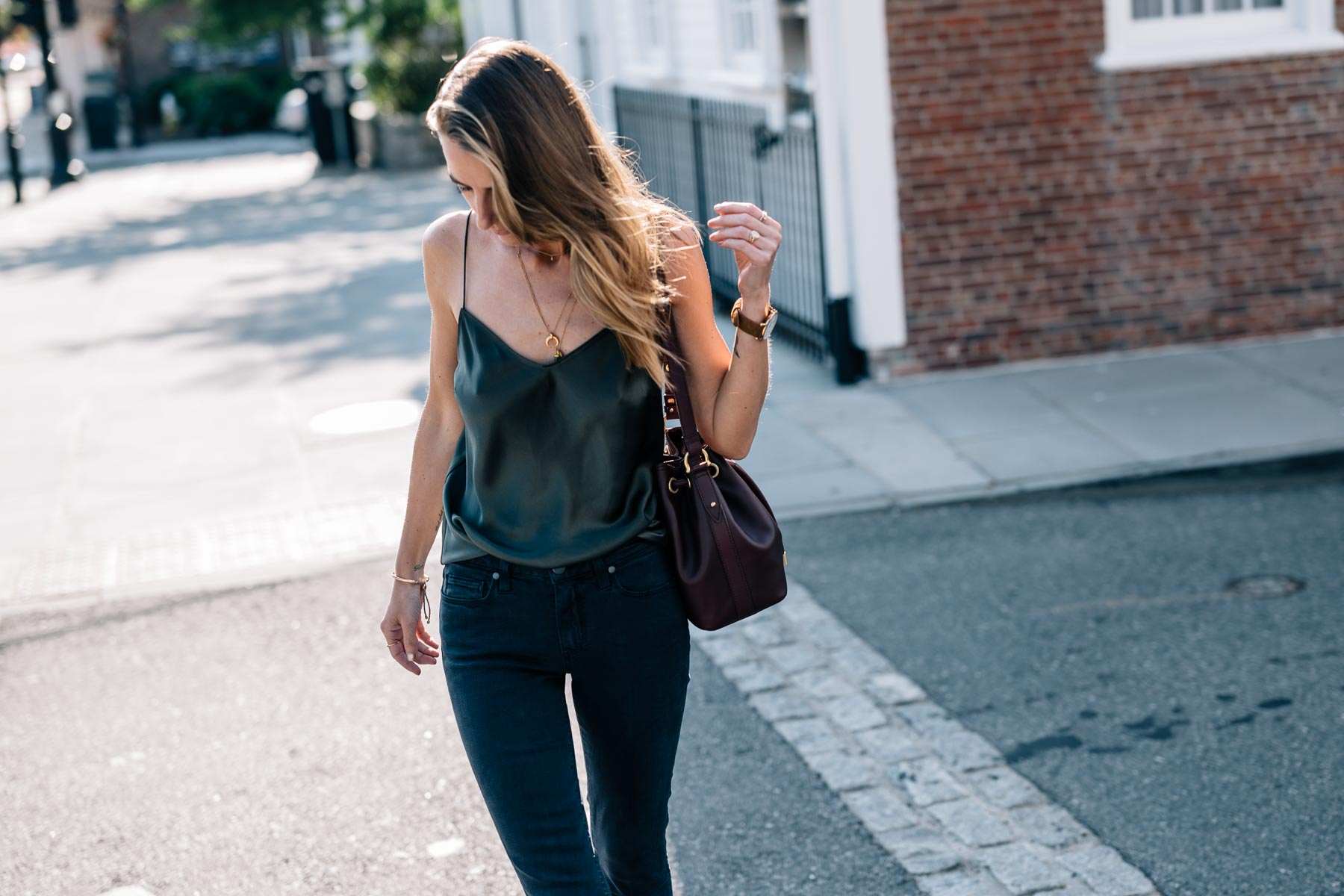 Jess Ann Kirby wears the Paige Cicely Silk Tank and Brahmin Isabelle Southcoast Bag