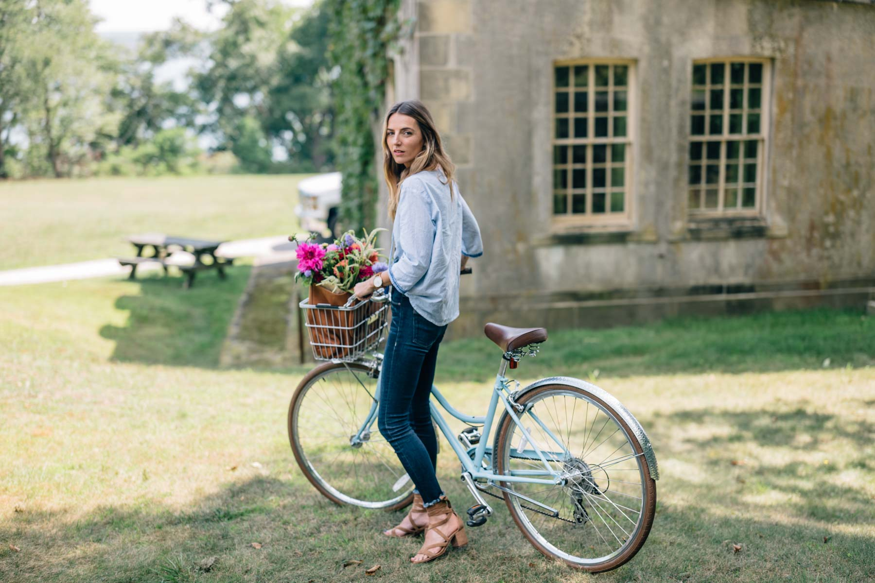 Jess Ann Kirby enjoys Spring in an embroidered blouse and jeans with a bouquet of seasonal flowers