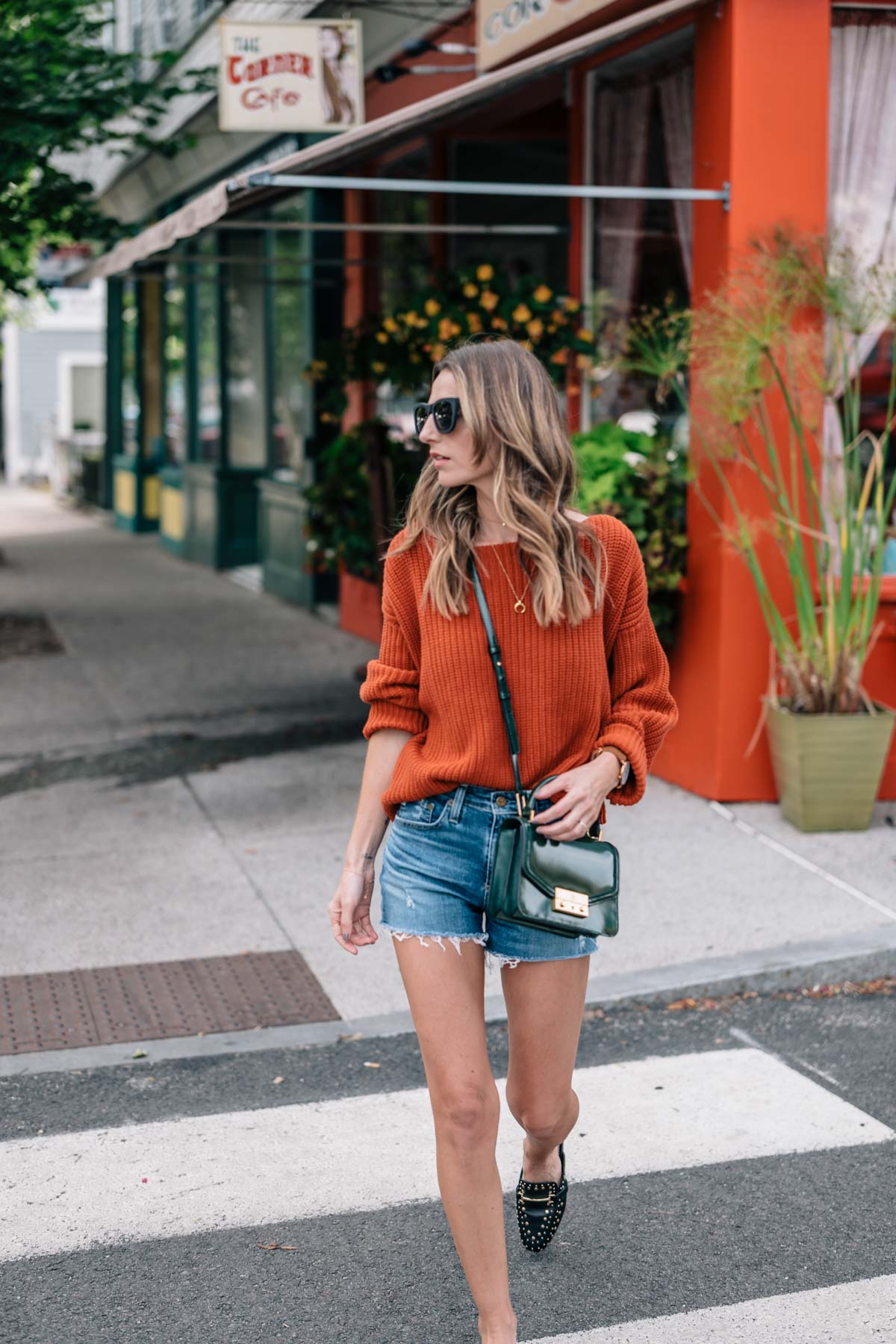 Jess Ann Kirby fall color trend street style in a chunky knit sweater, jean shorts, and slides