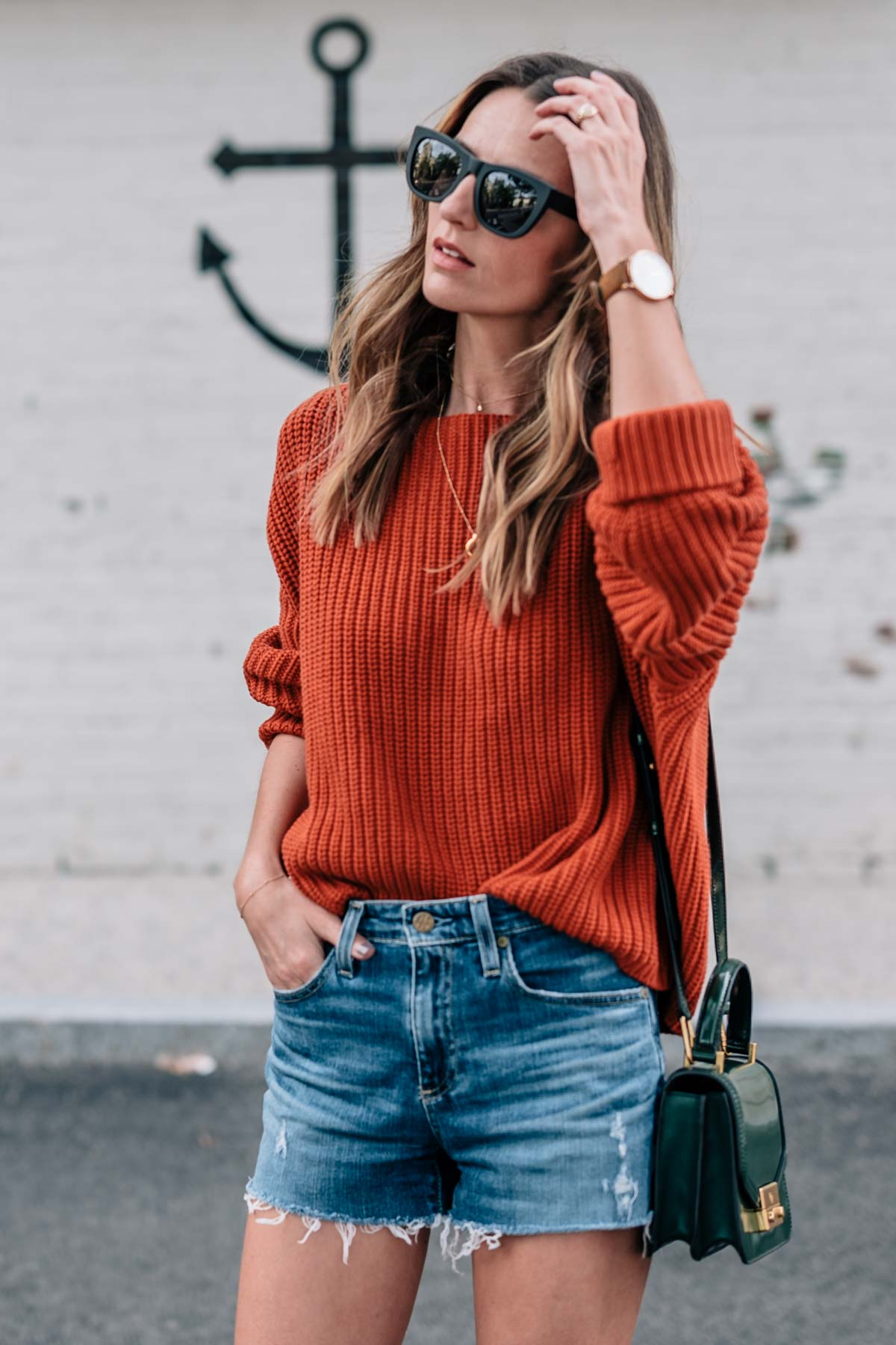 Jess Ann Kirby's fall style in a chunky knit sweater in pantone autumn maple and jean shorts