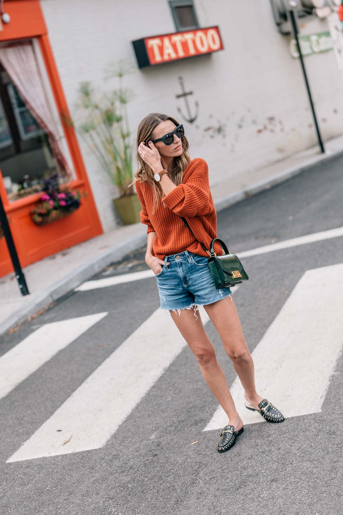 Jess Ann Kirby in Newport, RI wearing pantone autumn maple sweater, jean shorts, and sam edelman slides