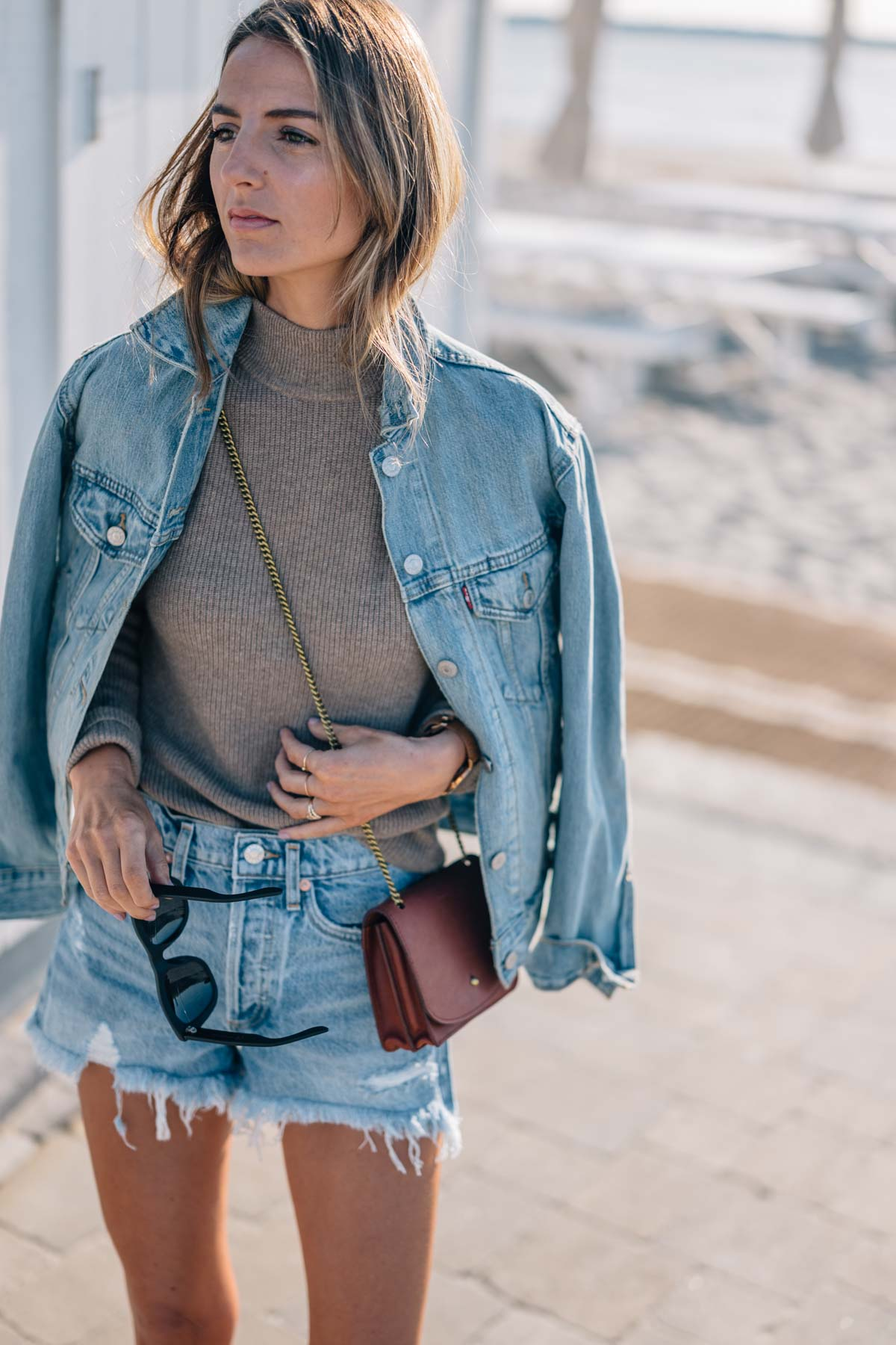 Jess Kirby shares transitional summer to fall style in a jean jacket, denim shorts and Velvet Bailee cashmere mock neck sweater