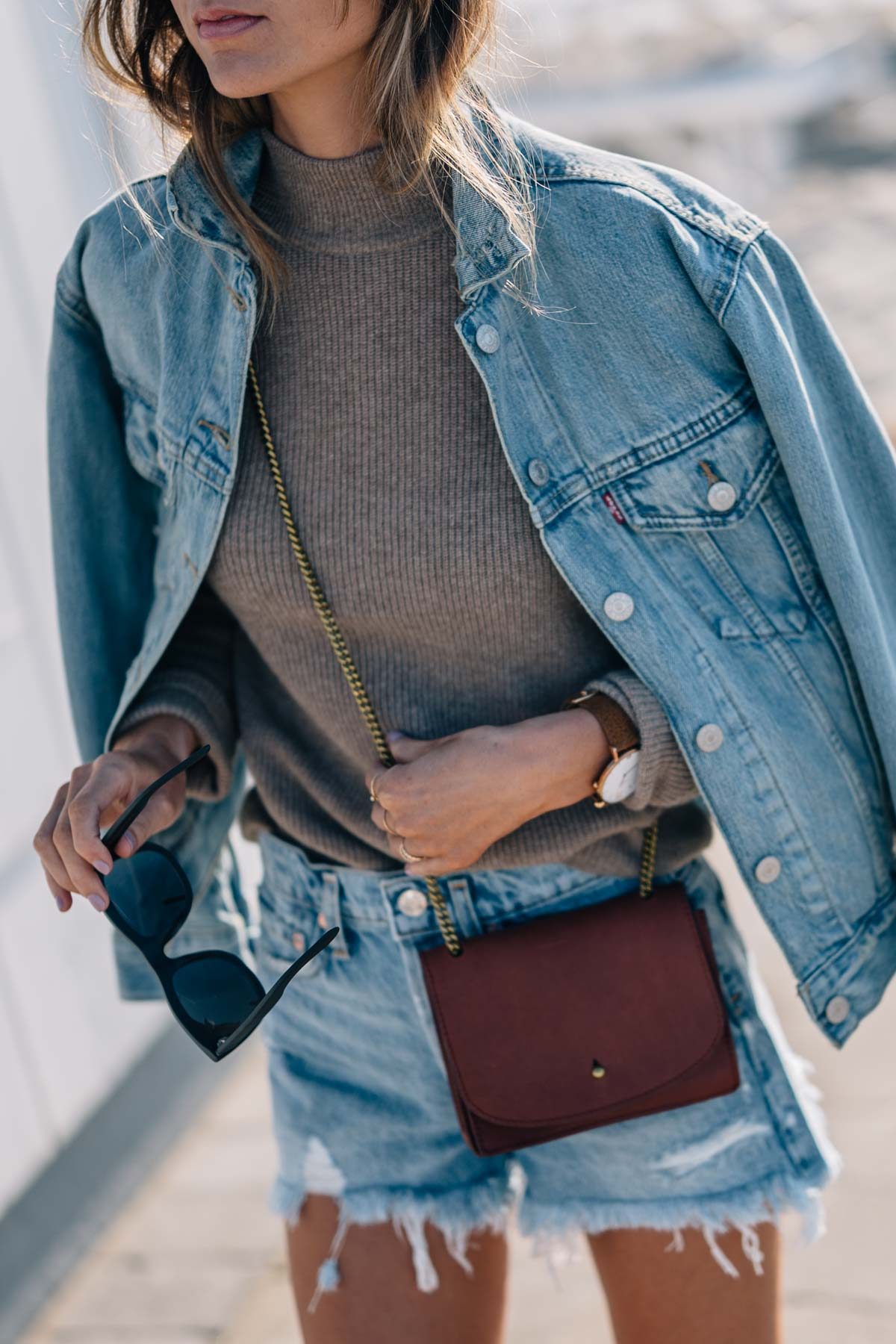 Jess Kirby wears a levis denim trucker jacket, cashmere sweater and denim shorts with a madewell crossbody bag