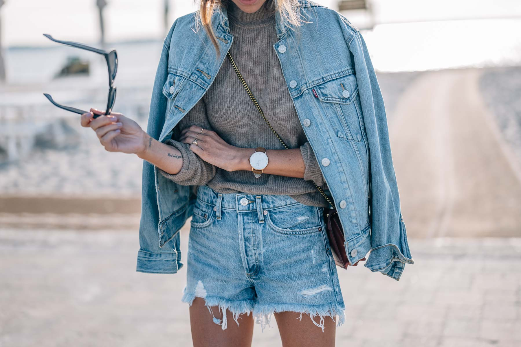 Jess Kirby wears denim on denim with a jean jacket, cashmere sweater and Agolde Parker vintage denim shorts
