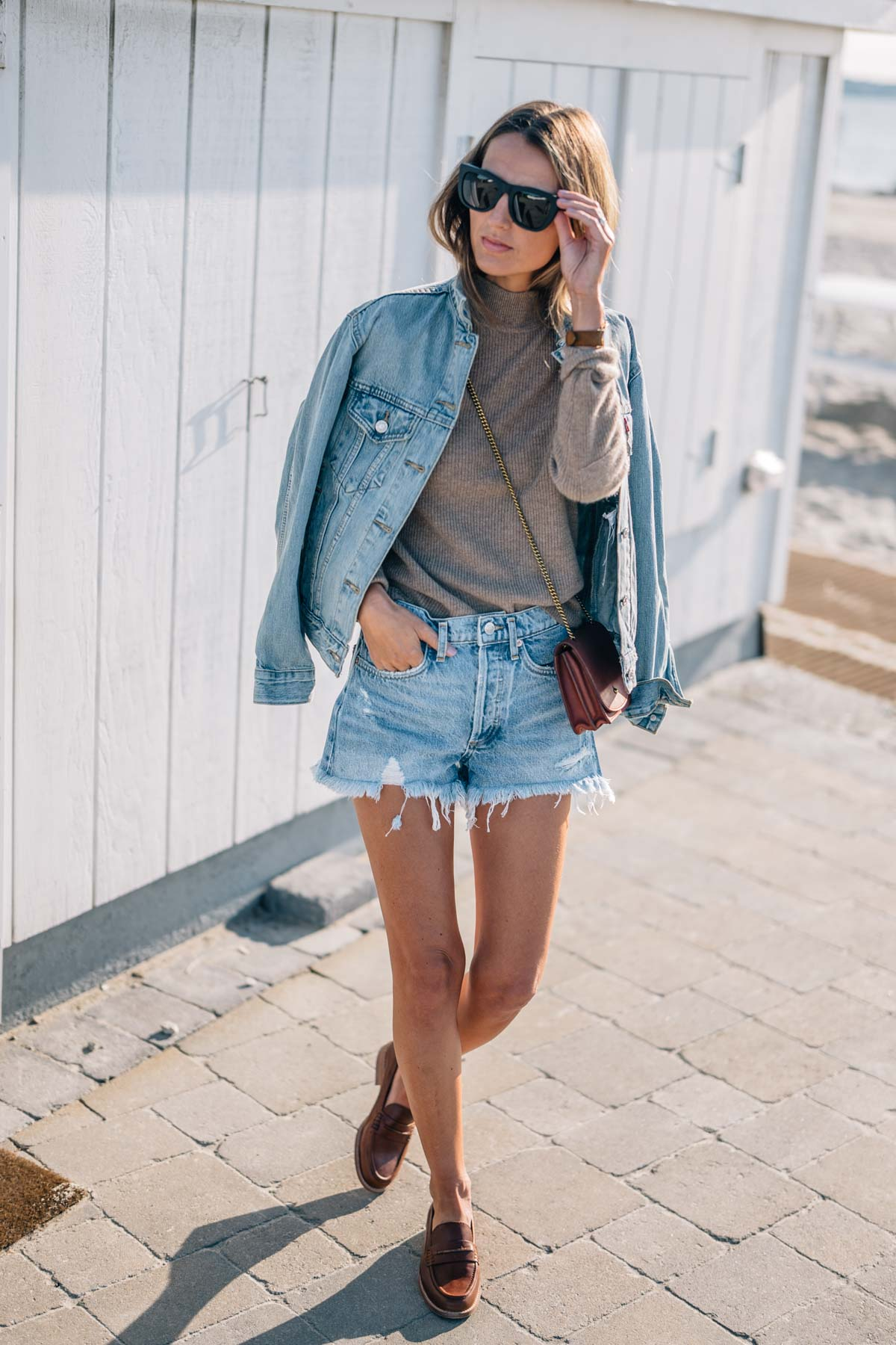 Jess Kirby wears super gals sunglasses, agolde parker vintage denim shorts and a cashmere sweater with madewell loafers