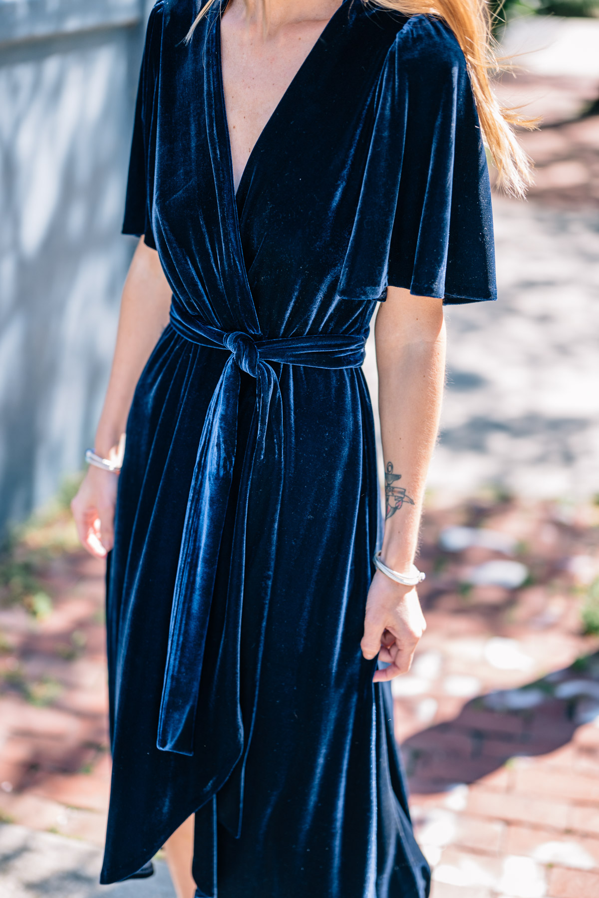 Jess Ann Kirby styles a velvet wrap midi dress by Donna Morgan for a fall wedding