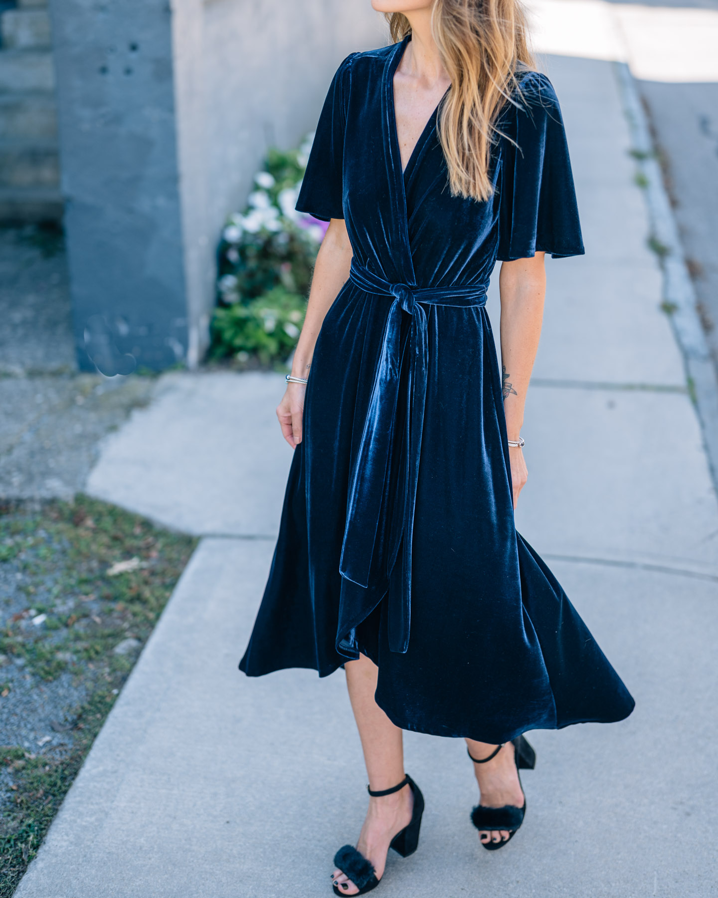Jess Ann Kirby wears a Donna Morgan velvet midi dress in navy with heels for a fall wedding