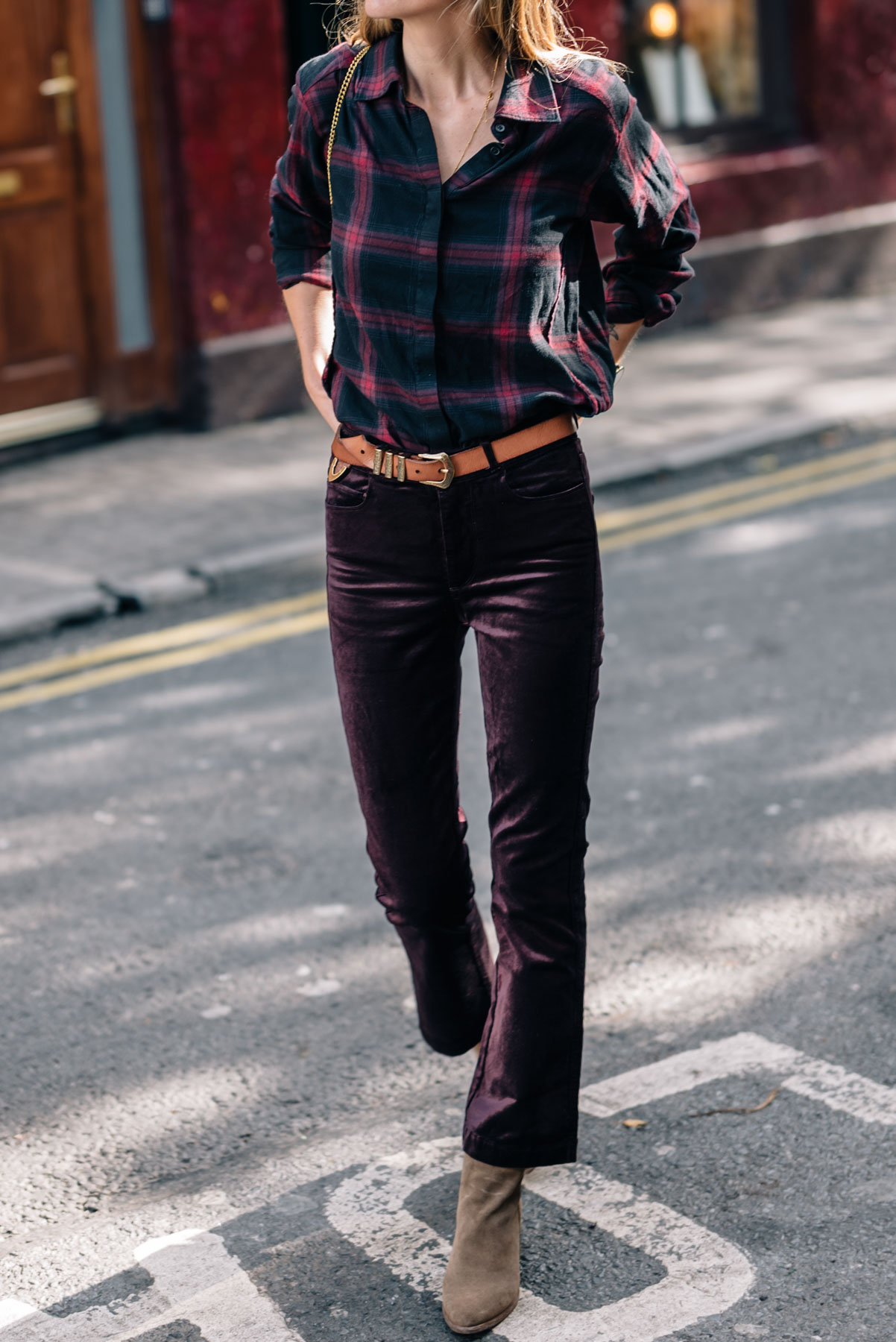 Jess Ann Kirby wears Paige Denim Velvet Pants with a Plaid Shirt and Leather Belt