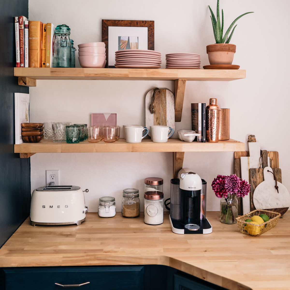 Jess Ann Kirby styles her kitchen open shelving with pops of pink and bright colors