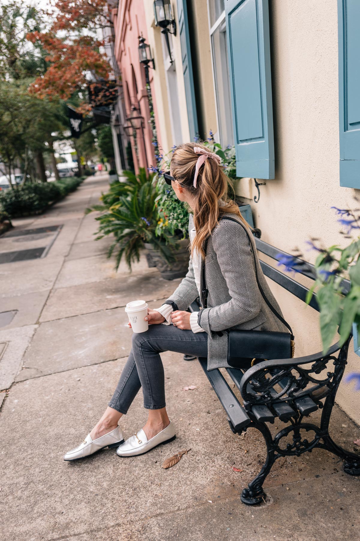 Jess Ann Kirby wears a blazer and skinny jeans on Rainbow Row in Charleston South Carolina