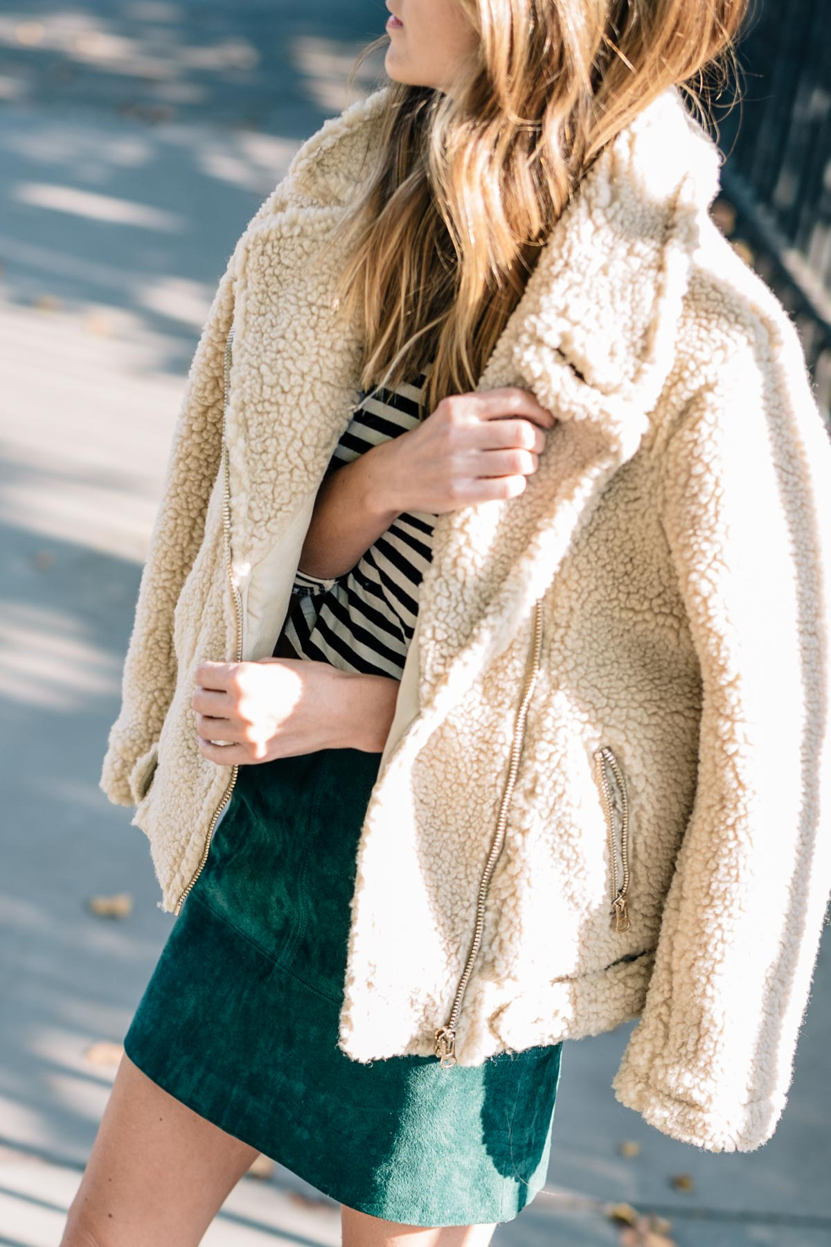 Jess Ann Kirby wears a H&M faux shearling moto jacket with a suede mini skirt for a cozy fall look