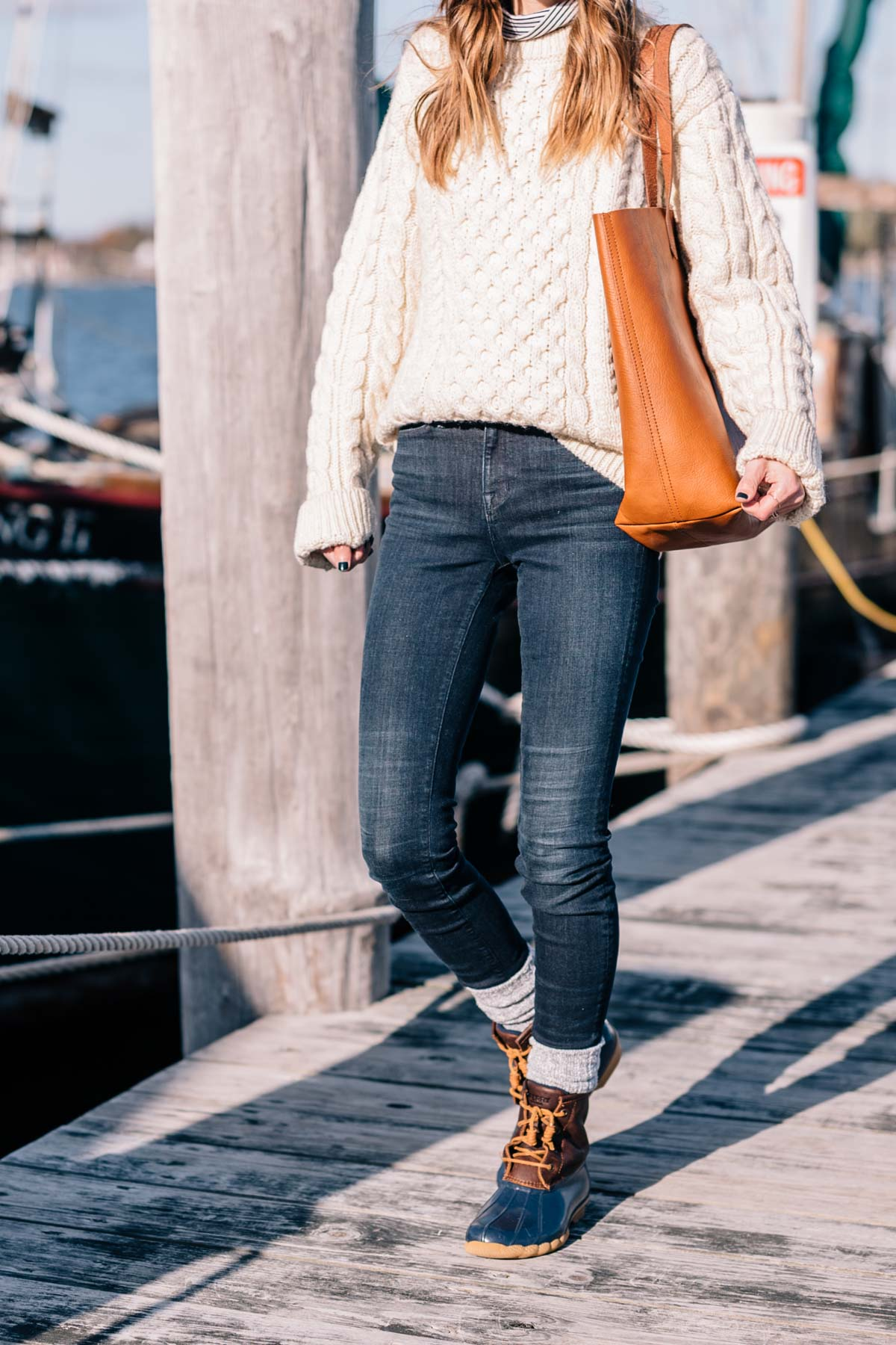 Jess Ann Kirby wears sperry duck boots and a LL Bean fisherman sweater with a made well tote to weather New England in the fall