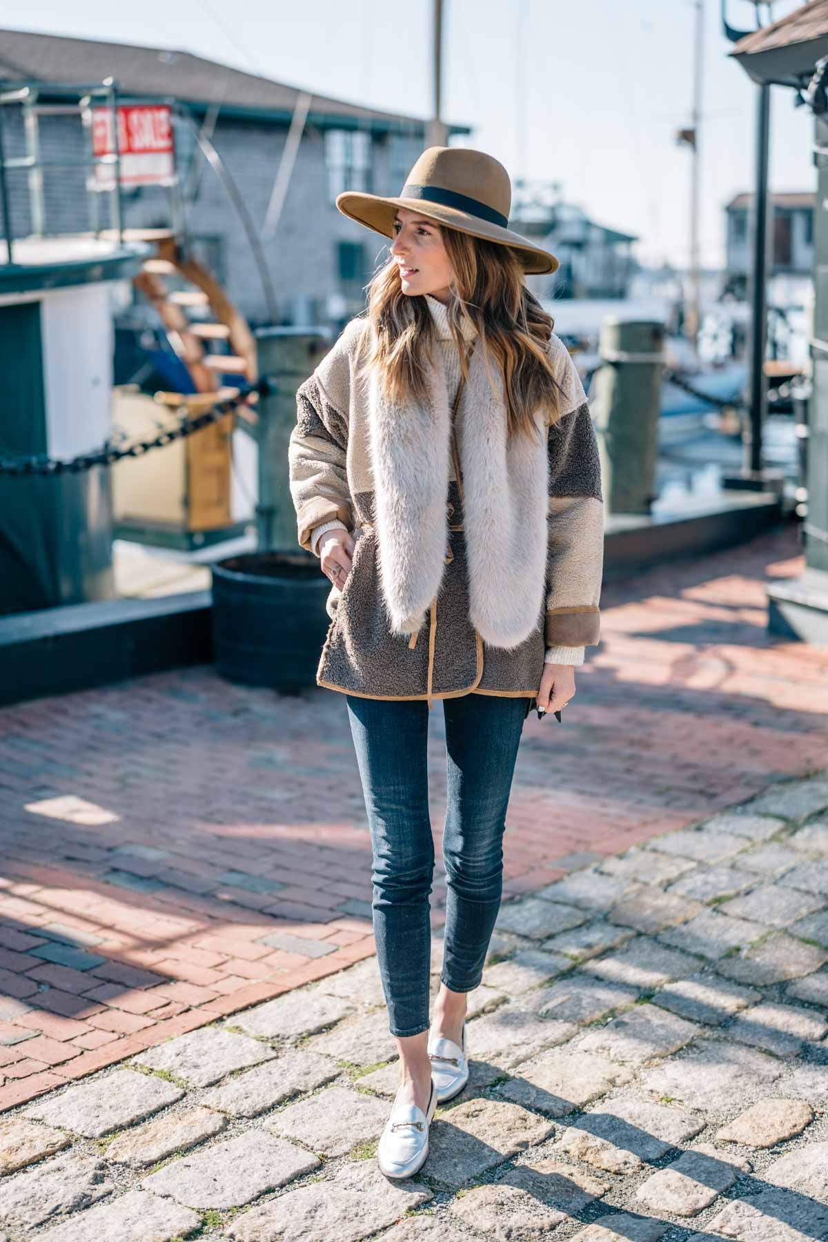 Jess Ann Kirby styles a faux fur scarf, skinny jeans and metallic loafers for a casual holiday look in Newport Rhode Island