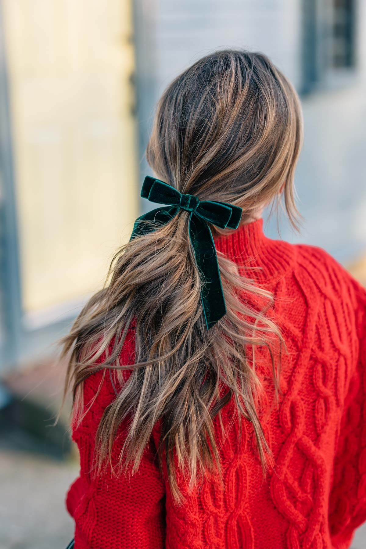 Jess Ann Kirby's balayage hair style for the holidays with a green velvet hair bow from J. Crew
