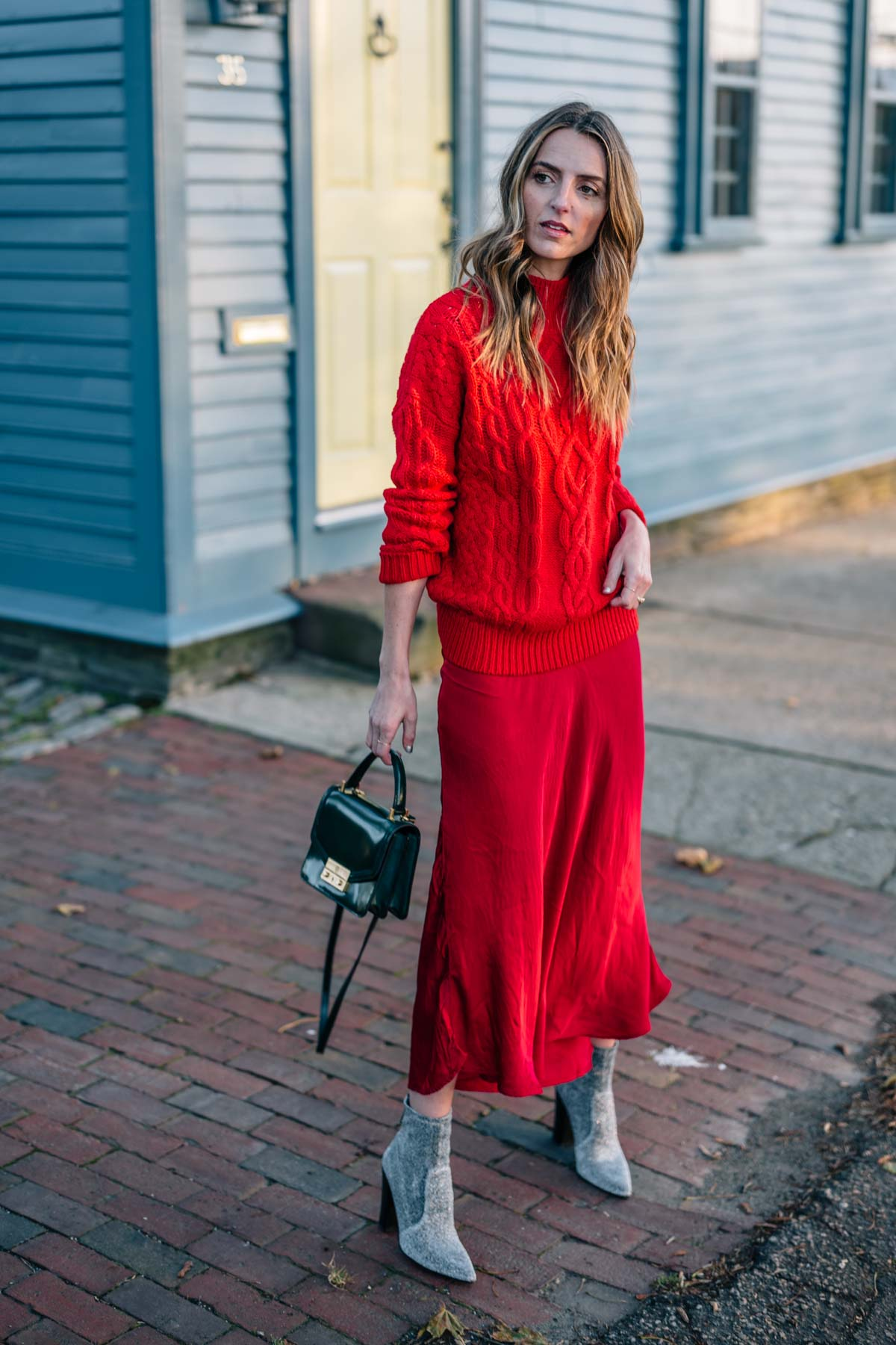 Jess Ann Kirby styles a holiday look with a red cable knit sweater and tory burch Juliette mini bag