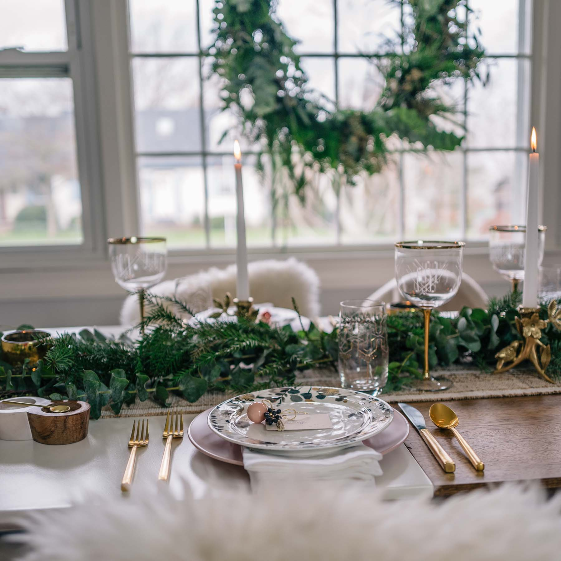 Jess Ann Kirby styles a rustic and minimal holiday tablescape with greenery and glassware from Anthropologie
