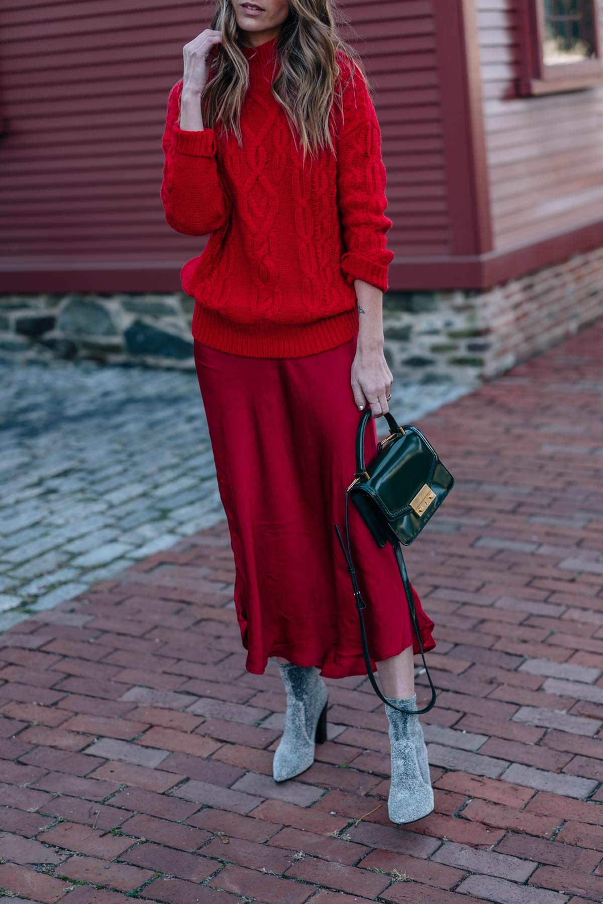 Jess Ann Kirby shares how to wear red on red this holiday season with a cable knit sweater, silk skirt and sparkle ankle boots