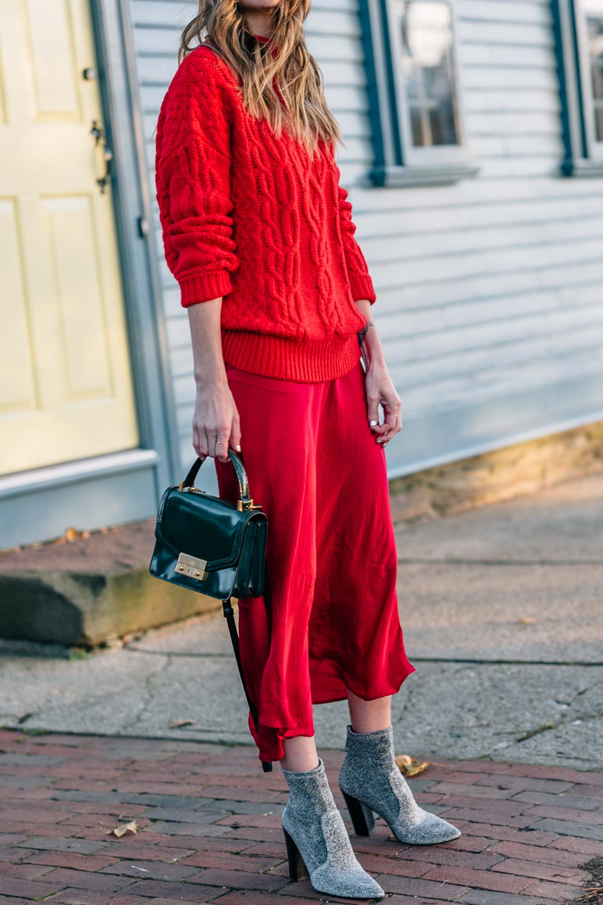 Jess Ann Kirby wears a red on red outfit with dolce vita lean stretch booties for the holidays