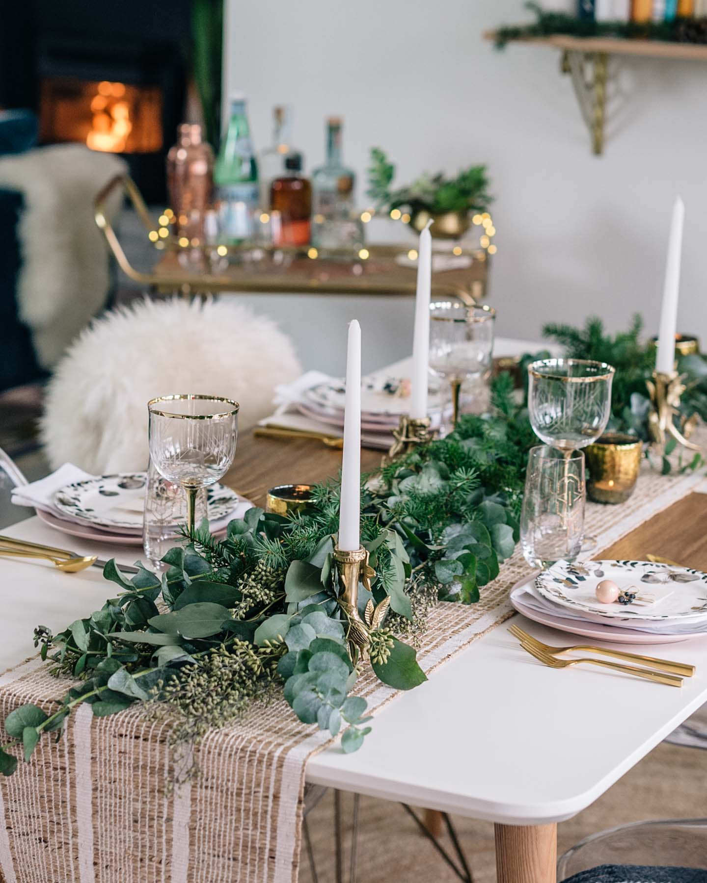 Jess Ann Kirby styles a rustic and minimal holiday tables cape with greenery and glassware from Anthropologie