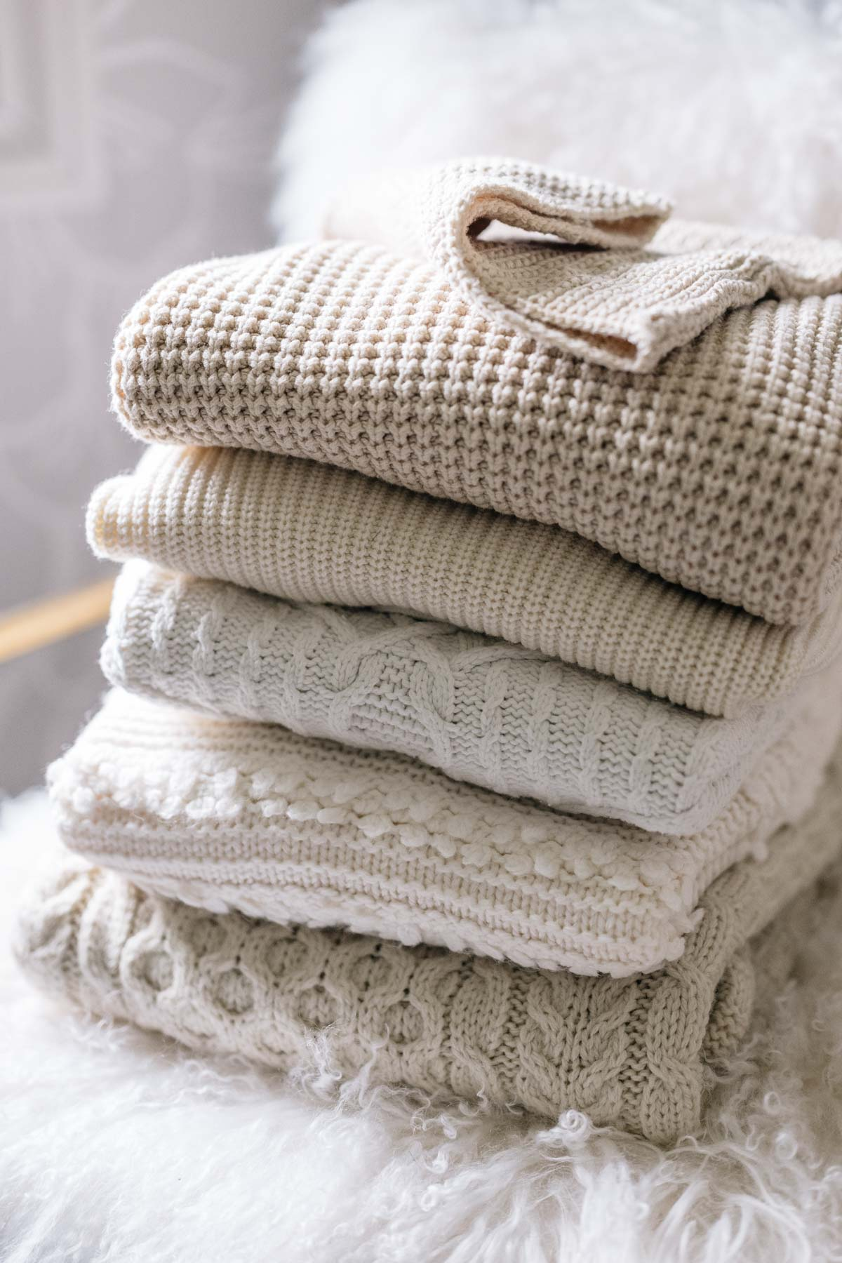 Jess Ann Kirby organizes her neutral colored chunky knit sweaters at her home in Rhode Island