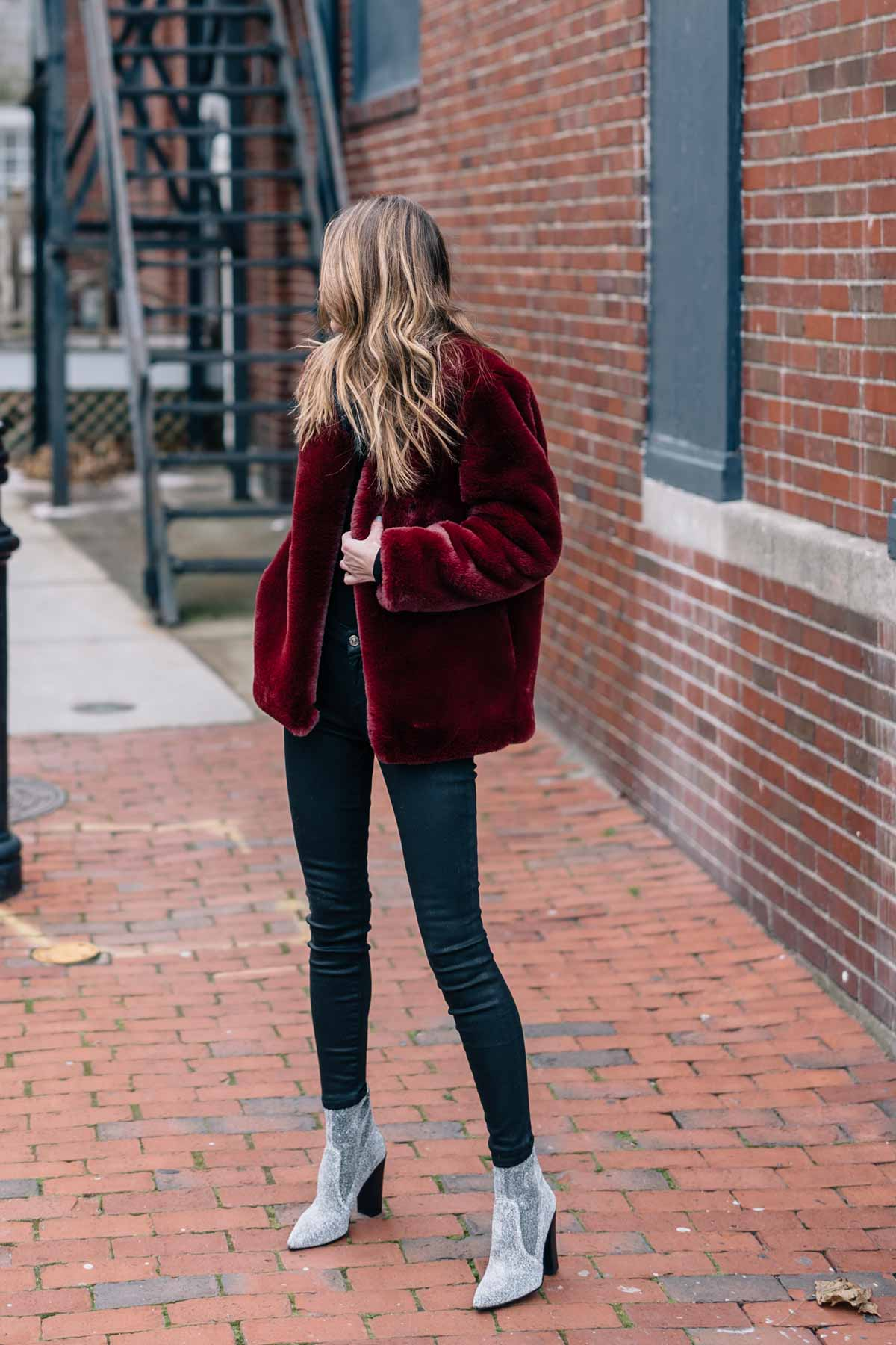Jess Ann Kirby wears a burgundy faux fur jacket with 7 for all man kind coated skinny jeans and sparkle booties from shop bop