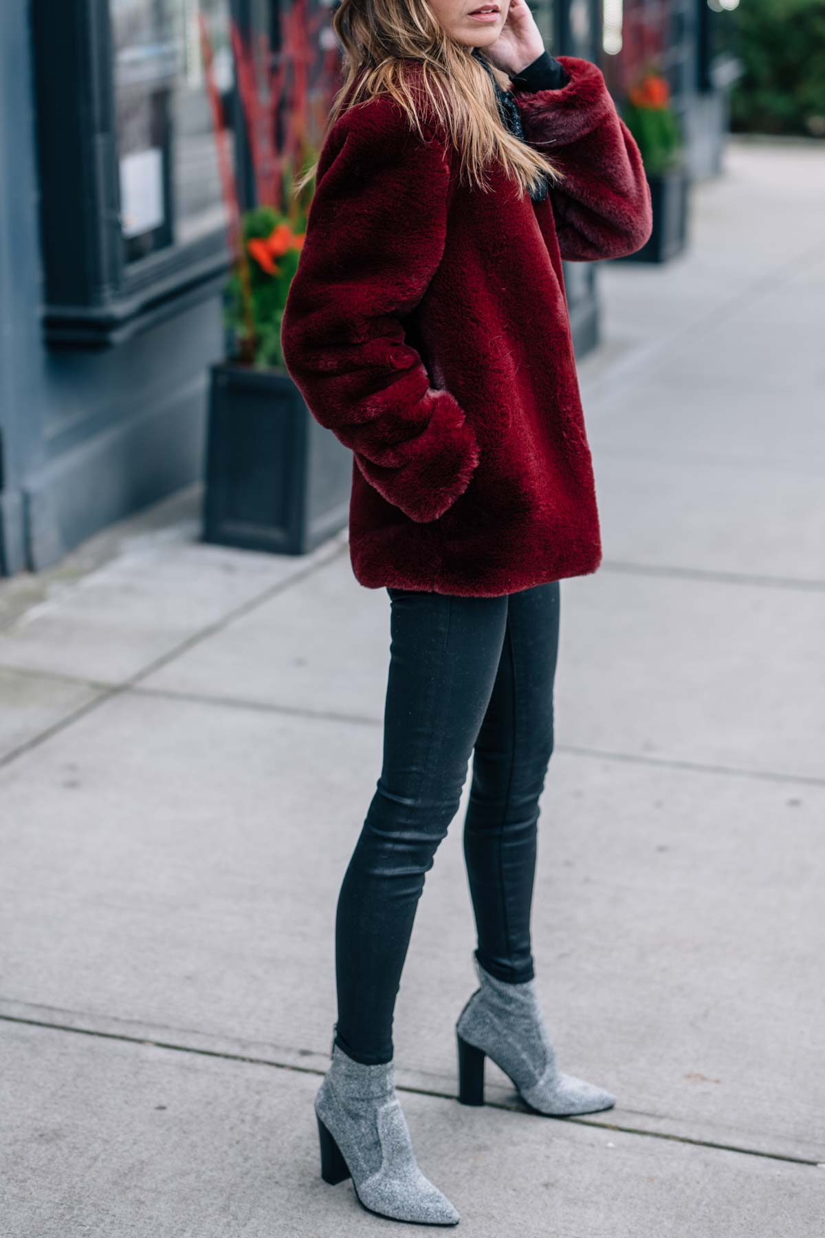 Jess Ann Kirby shares her holiday style this season in a burgundy Moon River faux fur jacket and Dolce Vita stretch sparkle booties