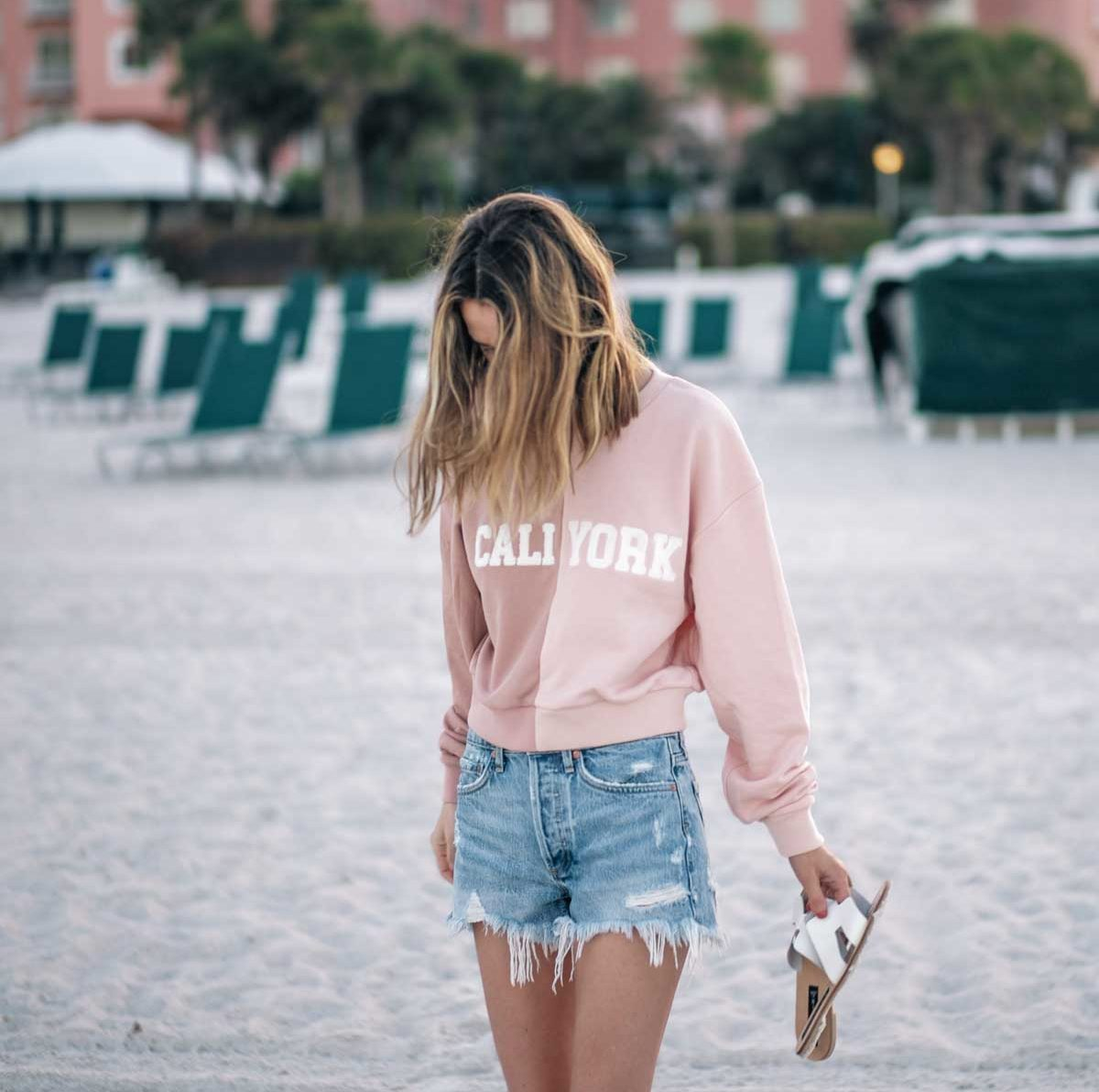 Jess Ann Kirby wears a Cynthia Rowley sweatshirt and Agolde vintage shorts on the beach in Saint Petersburg