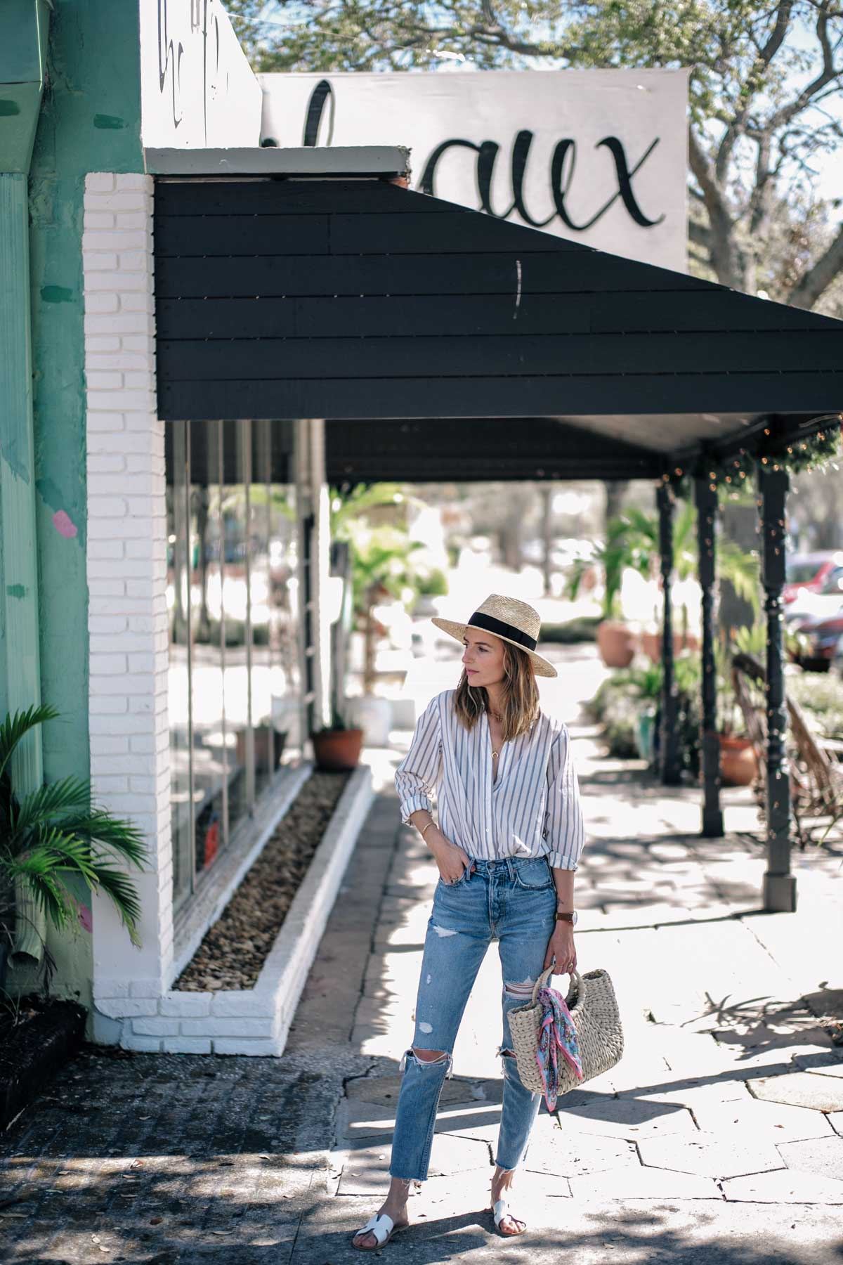 Jess Ann Kirby styles a striped button down with ripped jeans and a straw tote