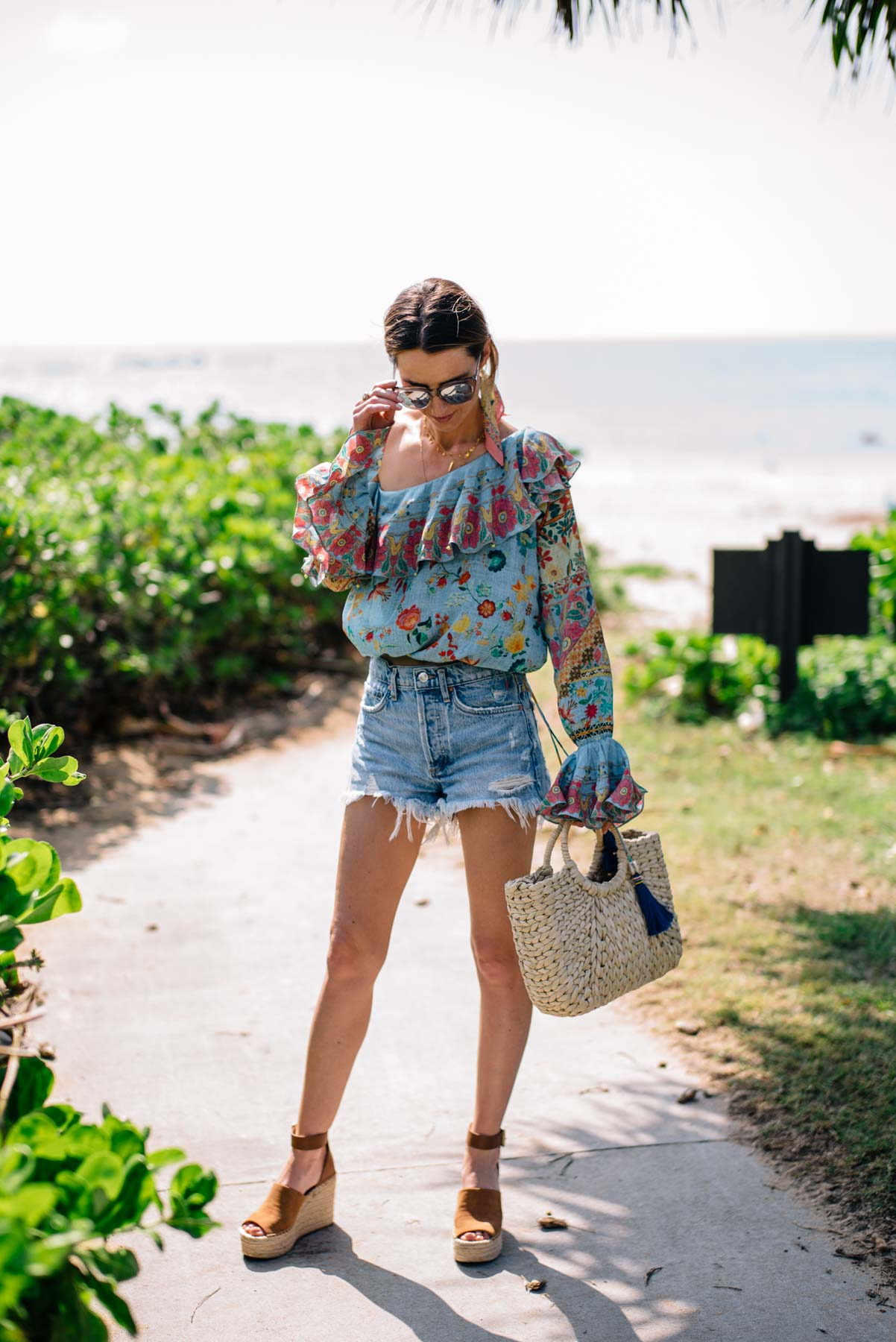 Jess Ann Kirby styles denim shorts for spring and summer with a colorful blouse and espadrilles