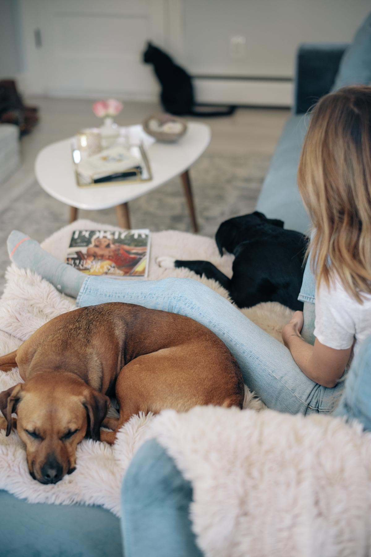 Jess Ann Kirby relaxes on her blue velvet sofa with a blush faux fur throw blanket