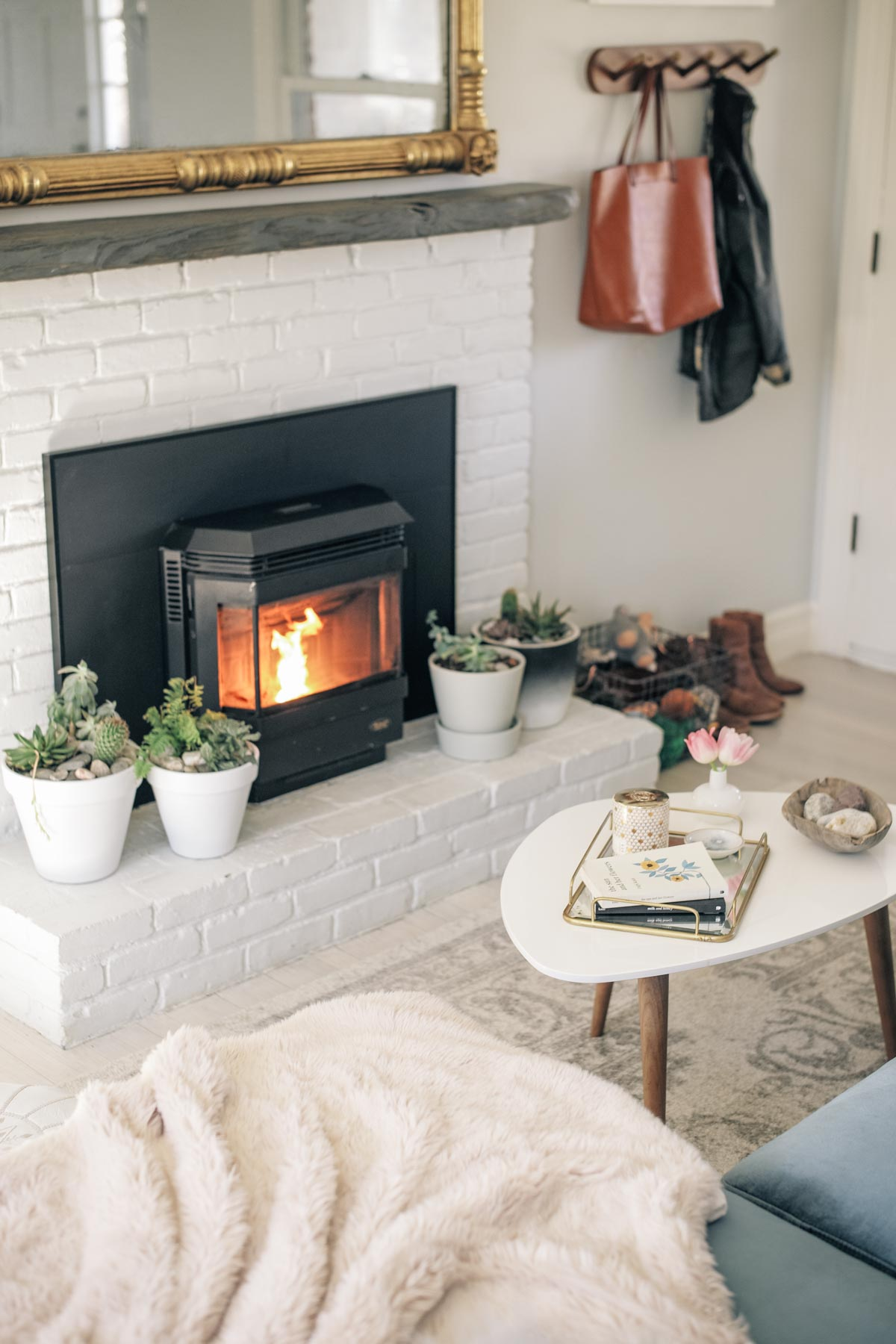 Jess Ann Kirby's home renovations includes a white brick mantle and pellet stove