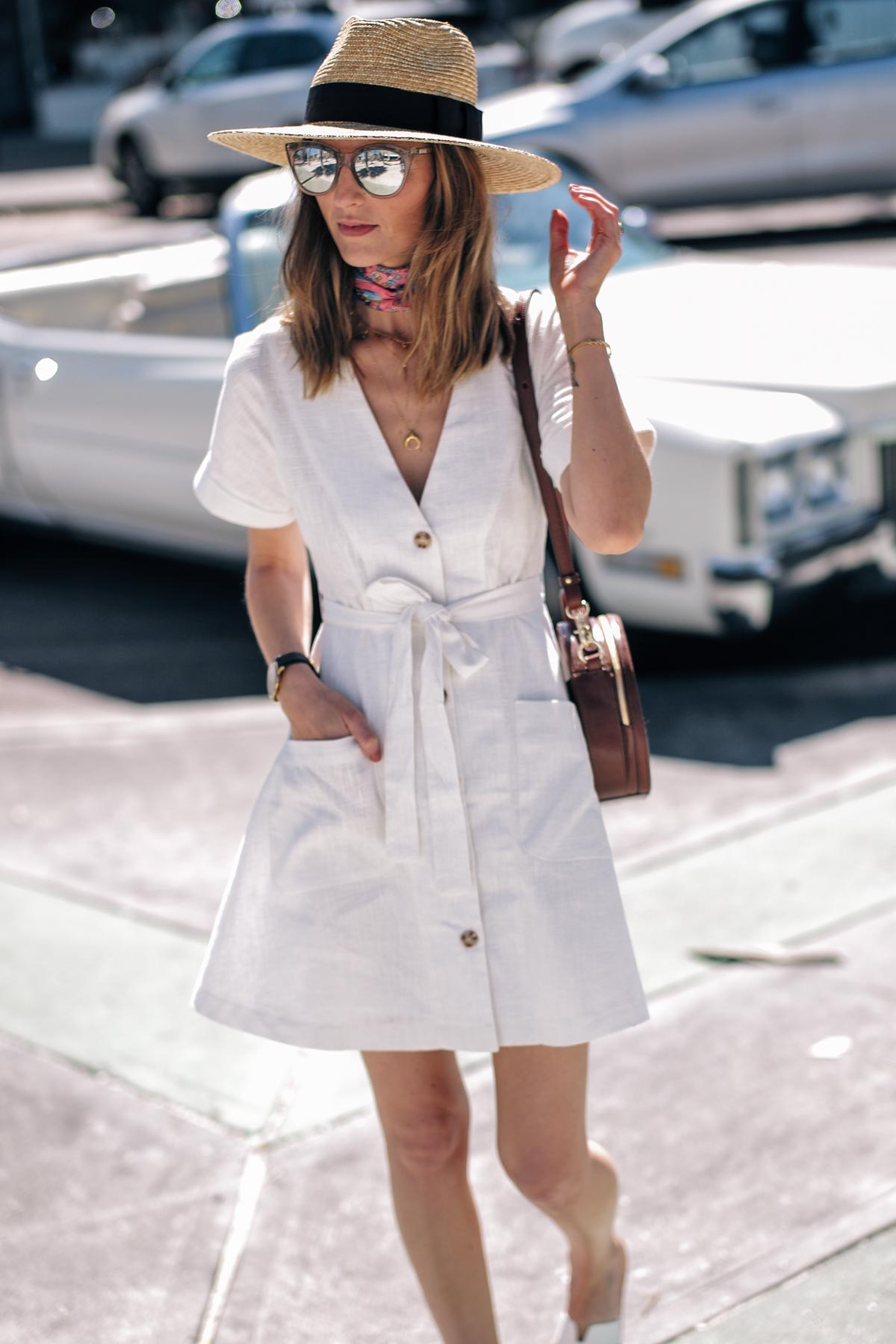 Jess Ann Kirby throws on a white linen dress and Brahmin crossbody to soak up the sun in Saint Petersburg, Florida
