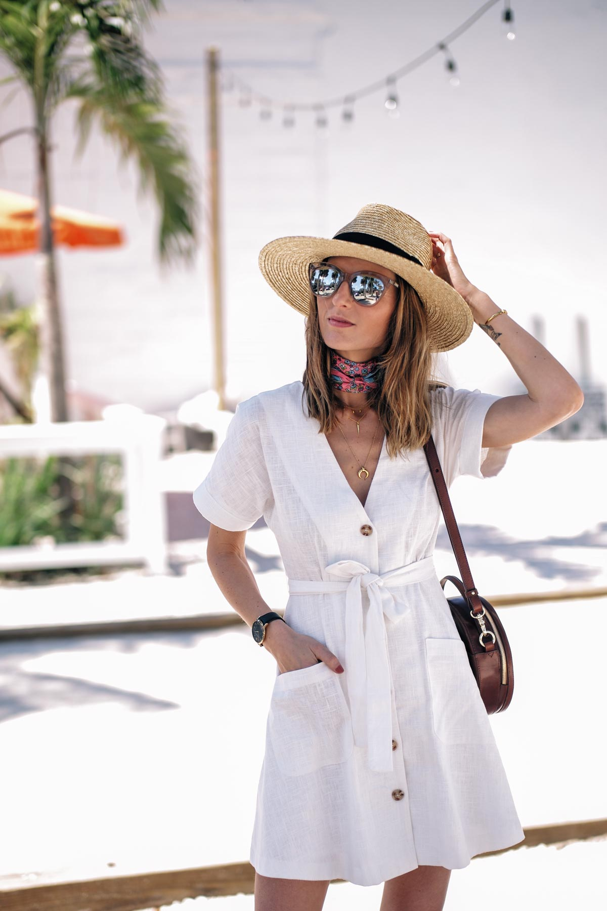 Jess Ann Kirby explores Saint Petersburg in a white linen dress with a straw hat and neck scarf