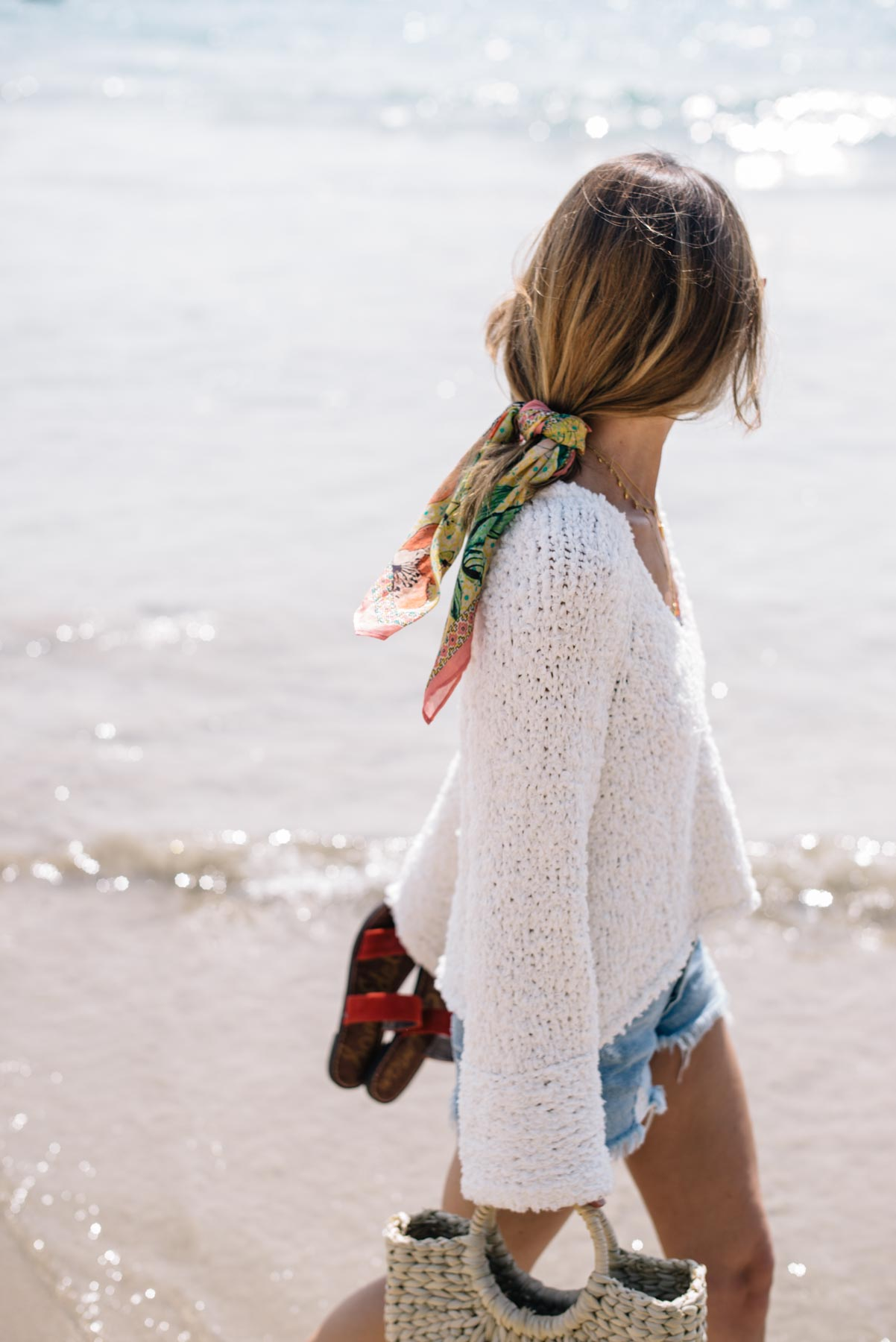 Jess Ann Kirby wears a Free People sand dune pullover and Agolde denim shorts in Hawaii