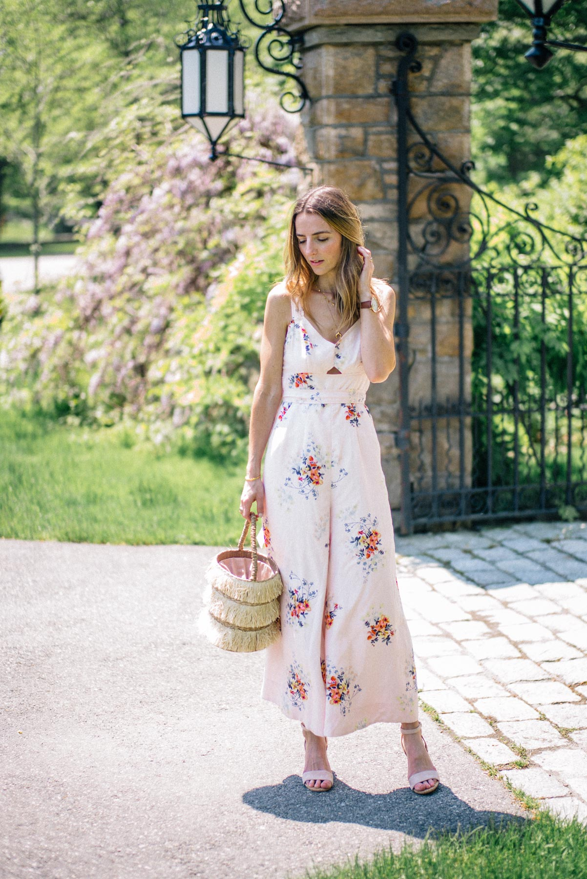 Jess Ann Kirby wears an Anthropologie jumpsuit and Kayu straw tote for a summer wedding look