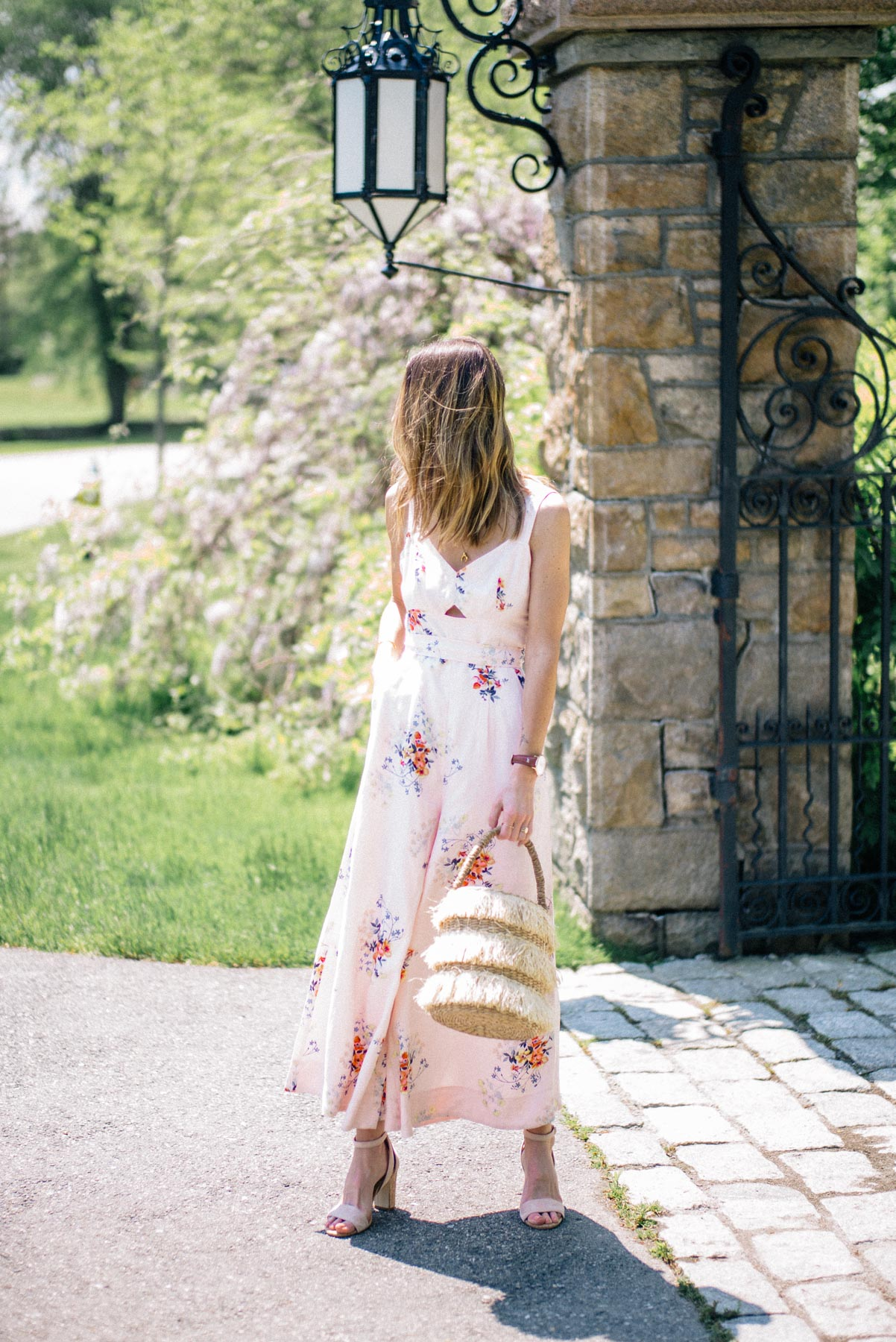 Jess Ann Kirby wears an Anthropologie jumpsuit and Kayu straw tote to a summer wedding