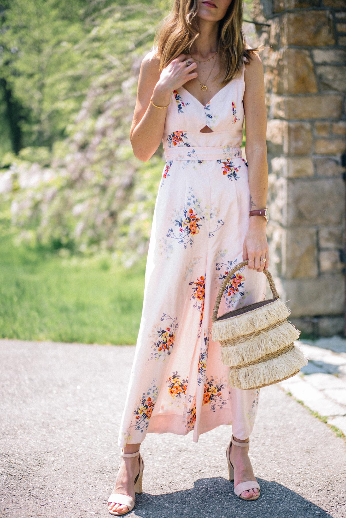 Jess Ann Kirby styles a floral printed jumpsuit with block heels and a straw tote