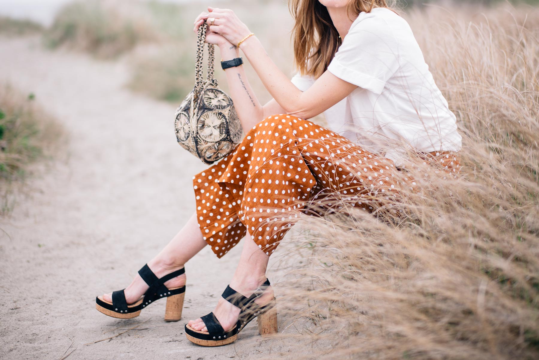 Jess Ann Kirby pairs wide leg polka dot pants with a statement bag and a simple boyfriend tee